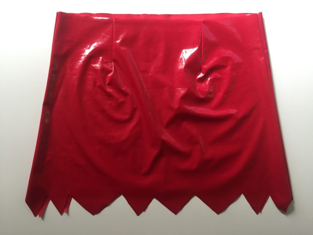Image of a red vinyl miniskirt with two waits darts and a jagged hem for the Catra costume