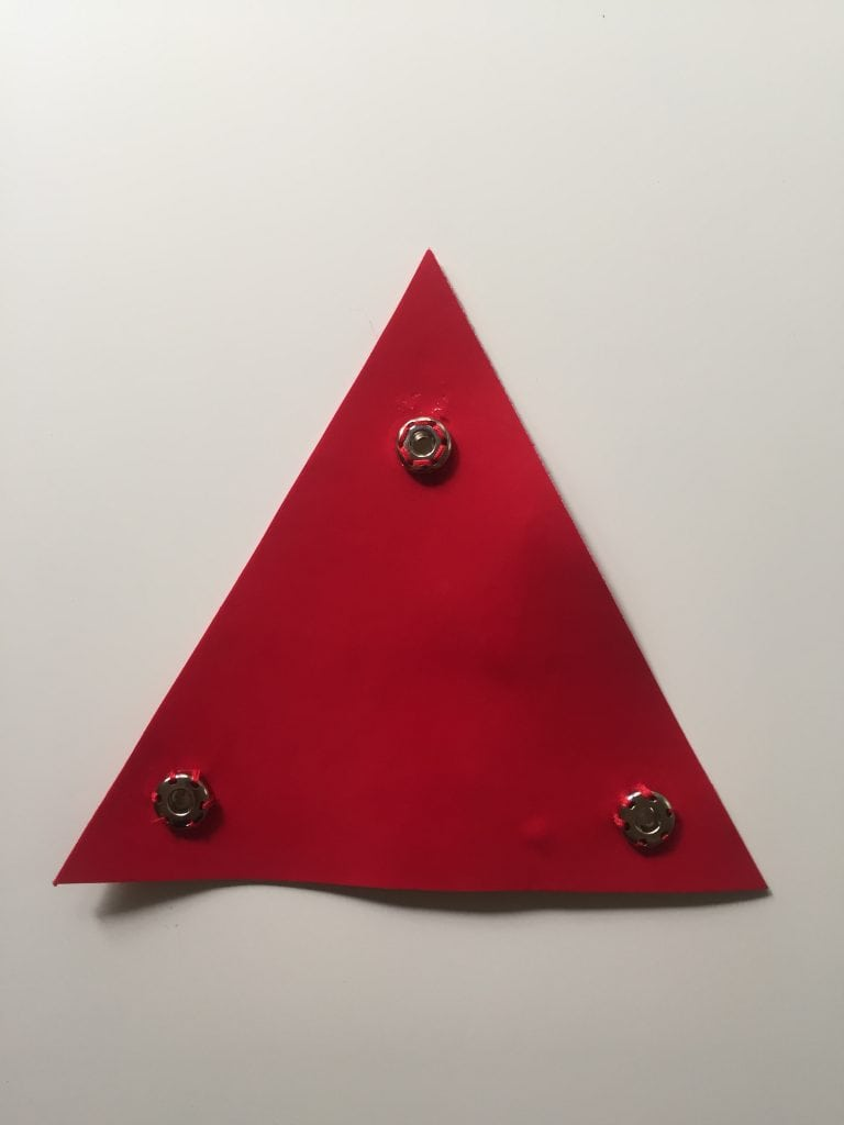 Detail of a vinyl triangle with three snap-on fasteners to attach the cape to the Catra costume corset