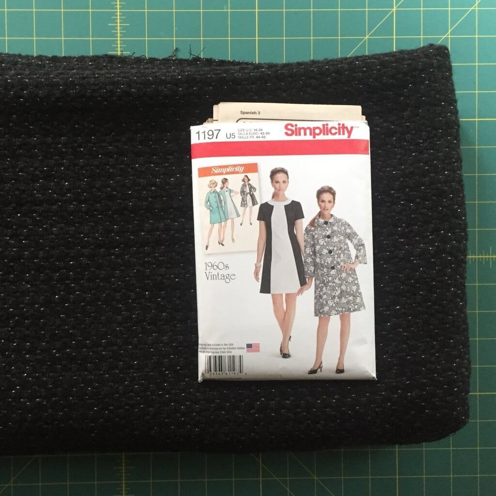 A picture of the pattern package and a cut of the wool blend on top of the cutting mat