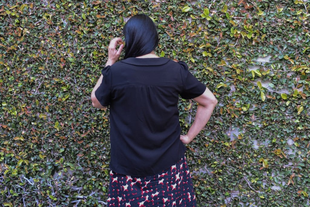 Image of a woman with long black hair with her back to the camera wearing a black blouse with a Peter Pan collar and a white, red, and black skirt in front of a wall covered in vines