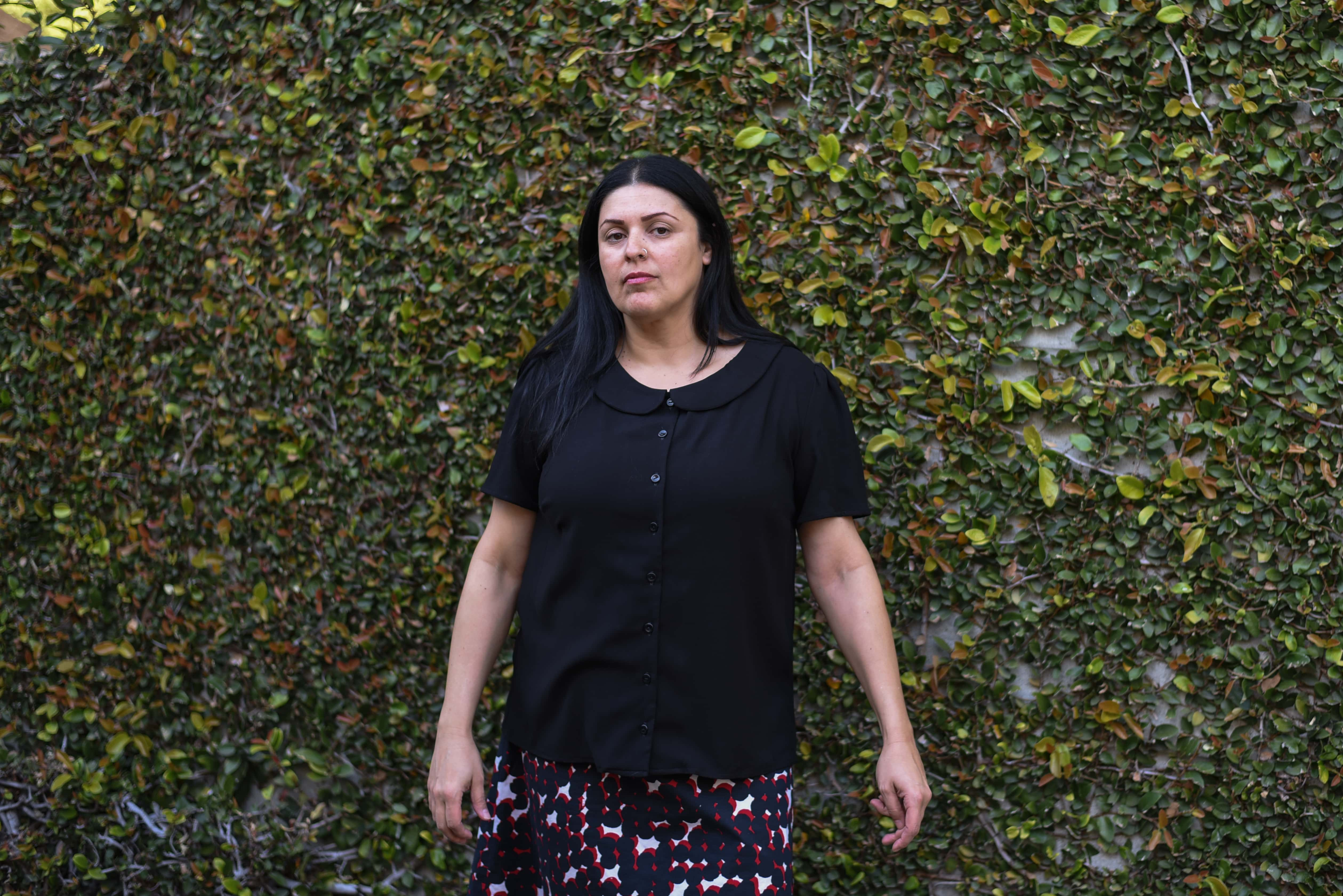 Image of a woman with long black hair wearing a black blouse with a Peter Pan collar and a white, red, and black skirt in front of a wall covered in vines