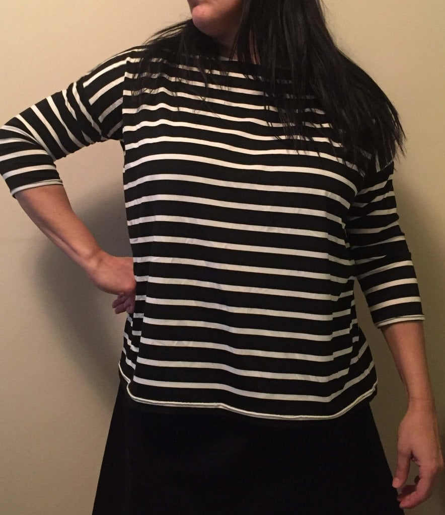 Woman with long black hair wearing a black-and-white stripes three-quarter sleeve T-shirt stands in front of a white wall