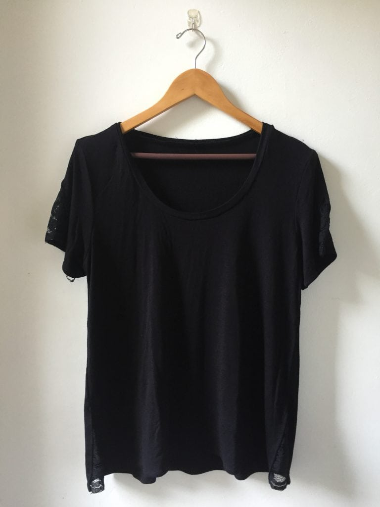 Image of a black T-shirt with lace sleeves details hanging from a hanger against a white wall