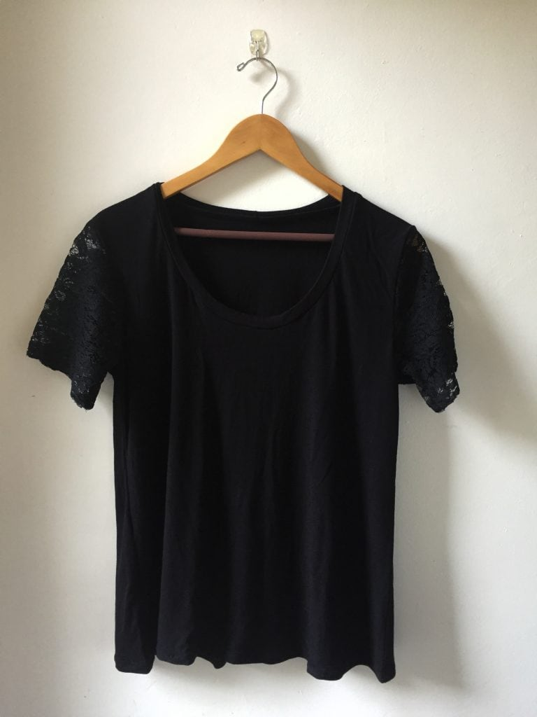 Image of a black T-shirt with lace sleeves hanging from a hanger against a white wall
