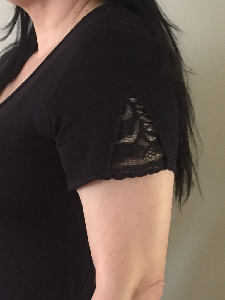 Detail image of a woman's arm to show the detail of the triangle of lace on the sleeve