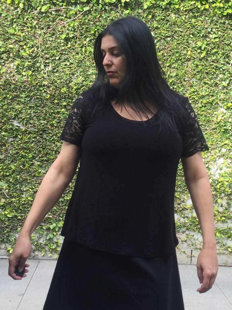 Image of a woman with long black hair wearing a T-shirt with lace sleeves and a black skirt standing in front of a wall covered in vines