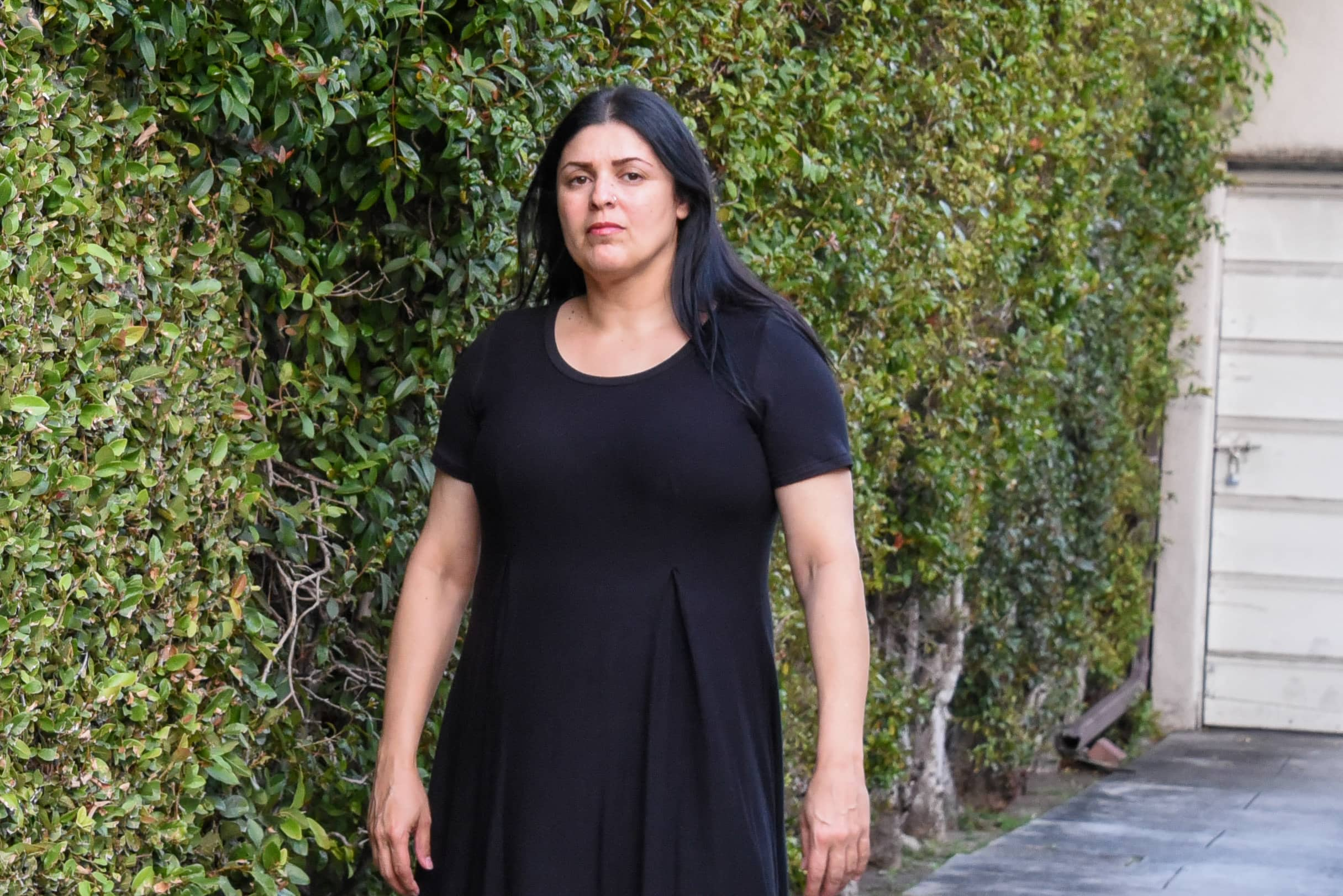 Image of me facing the camera, full body shot standing in front of a wall covered in tree vines, wearing a black Bexley dress