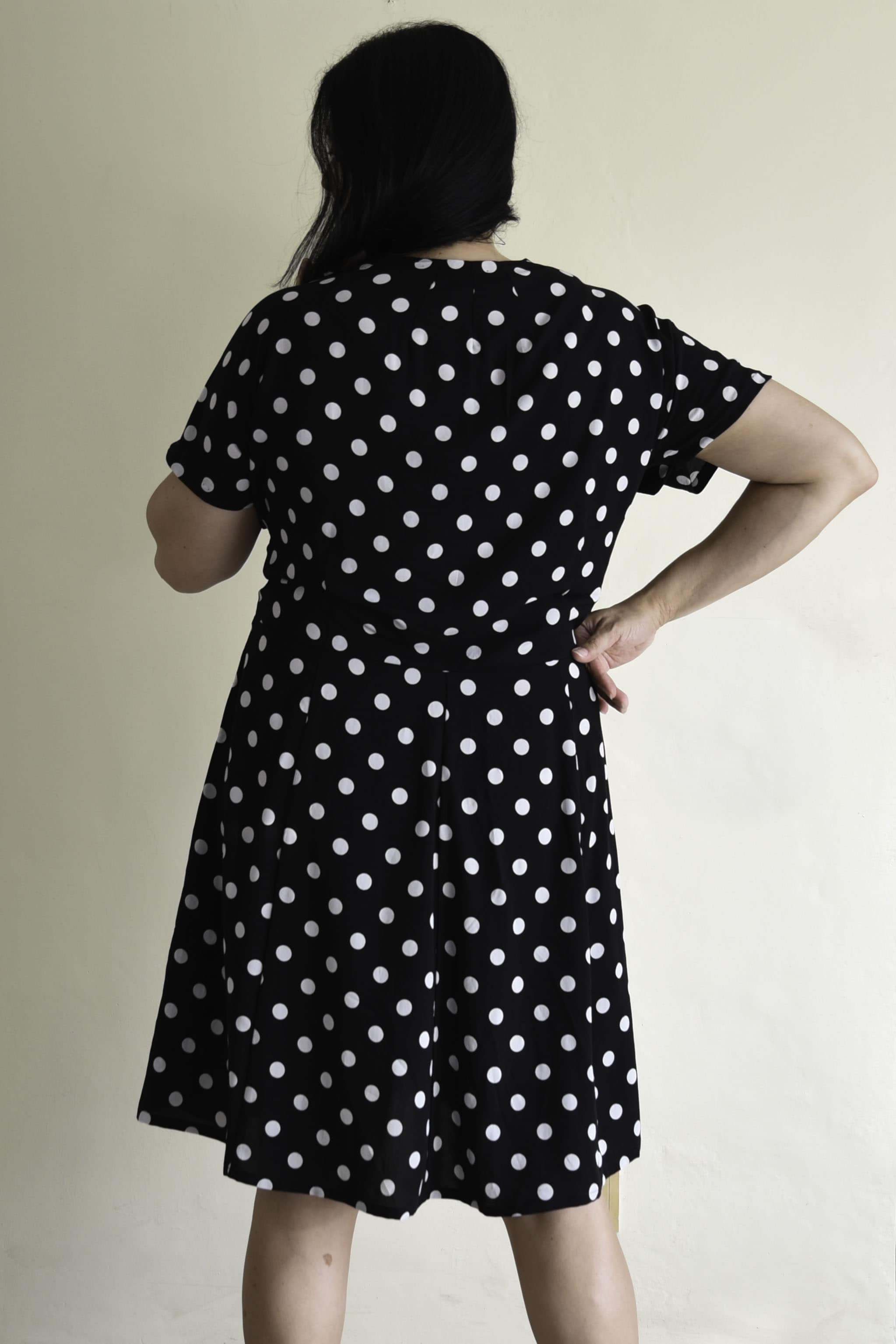 Image of woman with long black hair standing back facing the camera wearing a black and white polka dotted Myrna
