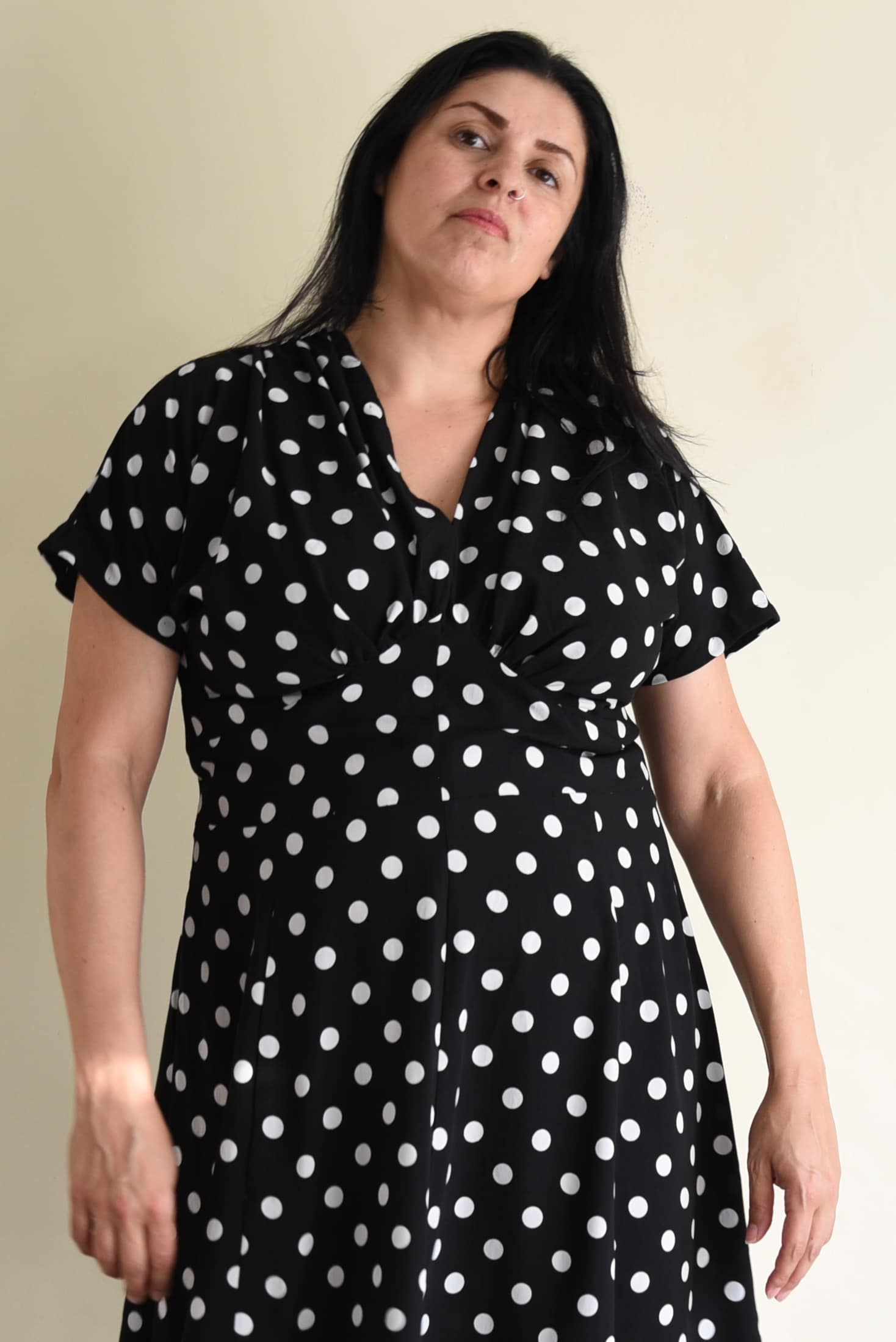 Image of woman with long black hair standing facing the camera wearing a black and white polka dotted Myrna