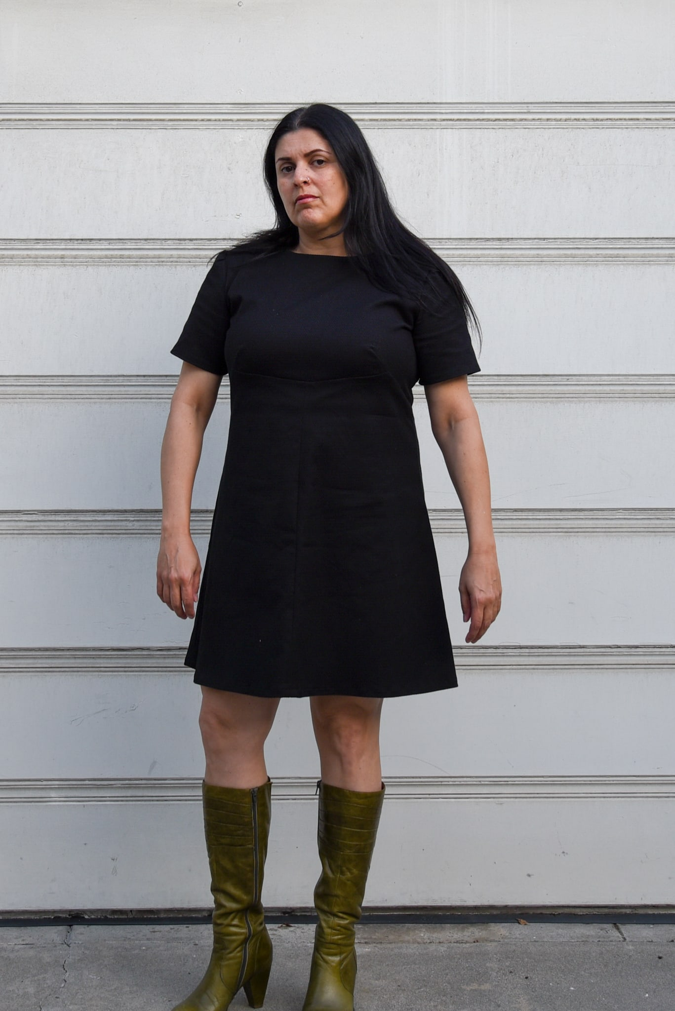 Image of woman standing in front of a garage door wearing Simplicity 3833, an A-line dress in black pique cotton and boots