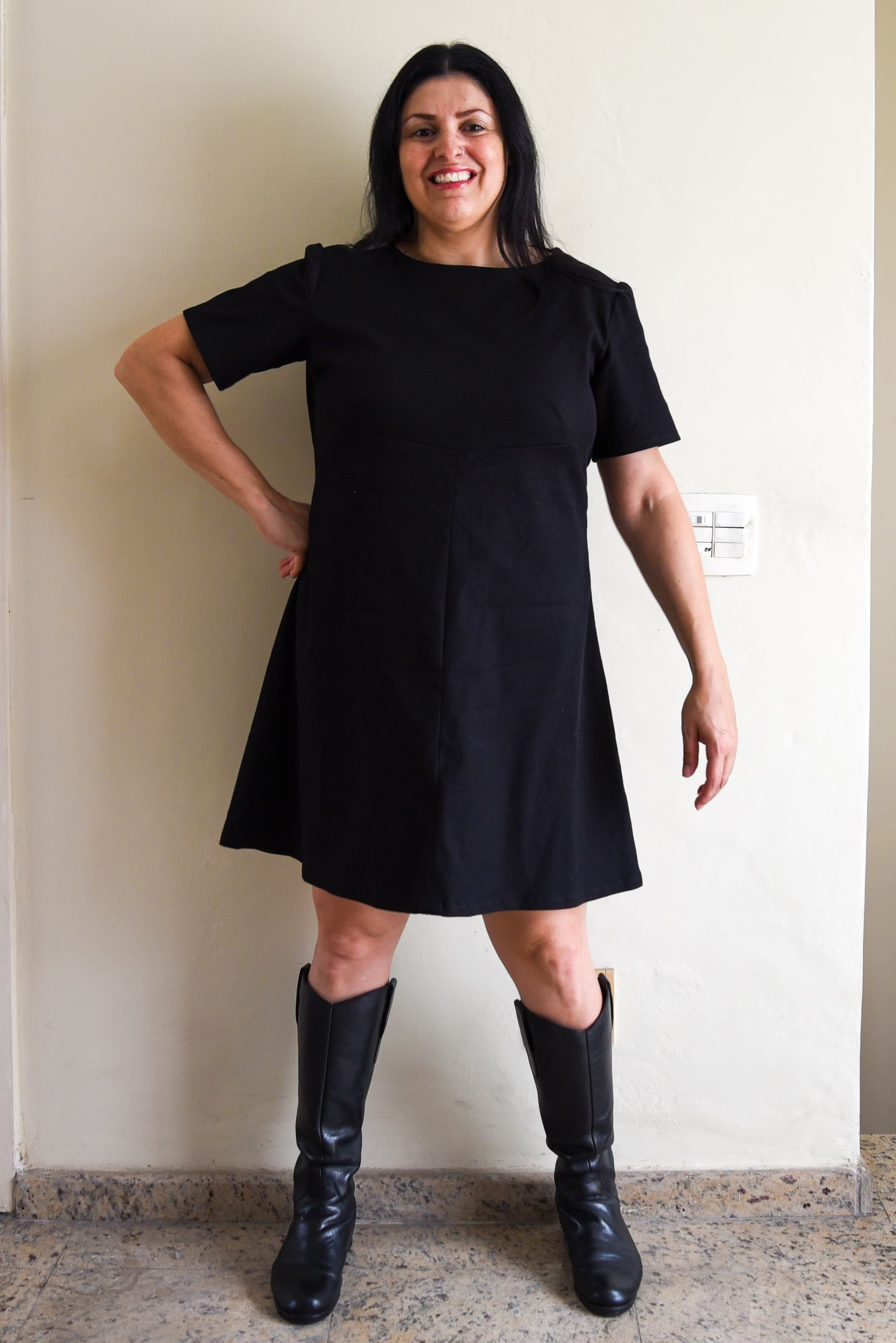Image of Paula standing in front of a wall, facing the camera, wearing Simplicity 3833, an A-line dress in black pique cotton and boots