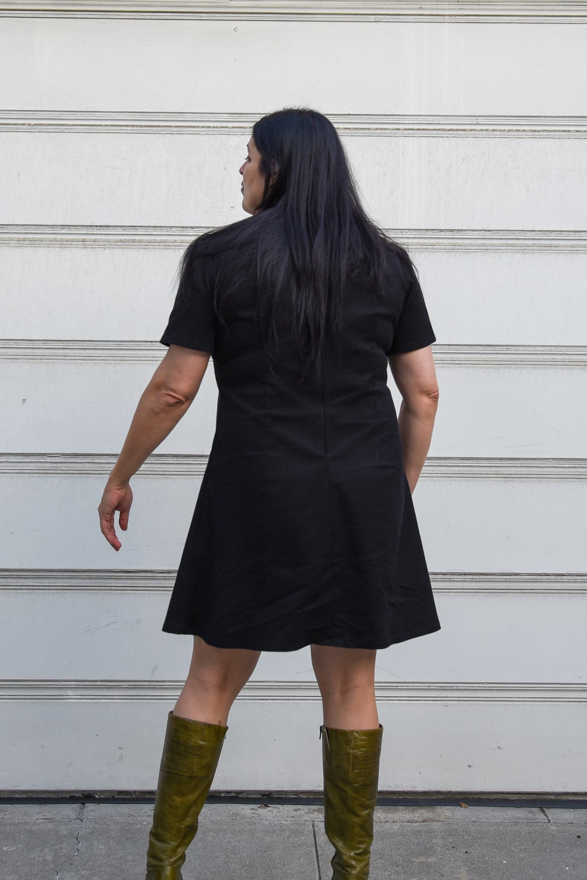 Image of woman standing in front of a garage door, back facing the camera, wearing Simplicity 3833, an A-line dress in black pique cotton and boots