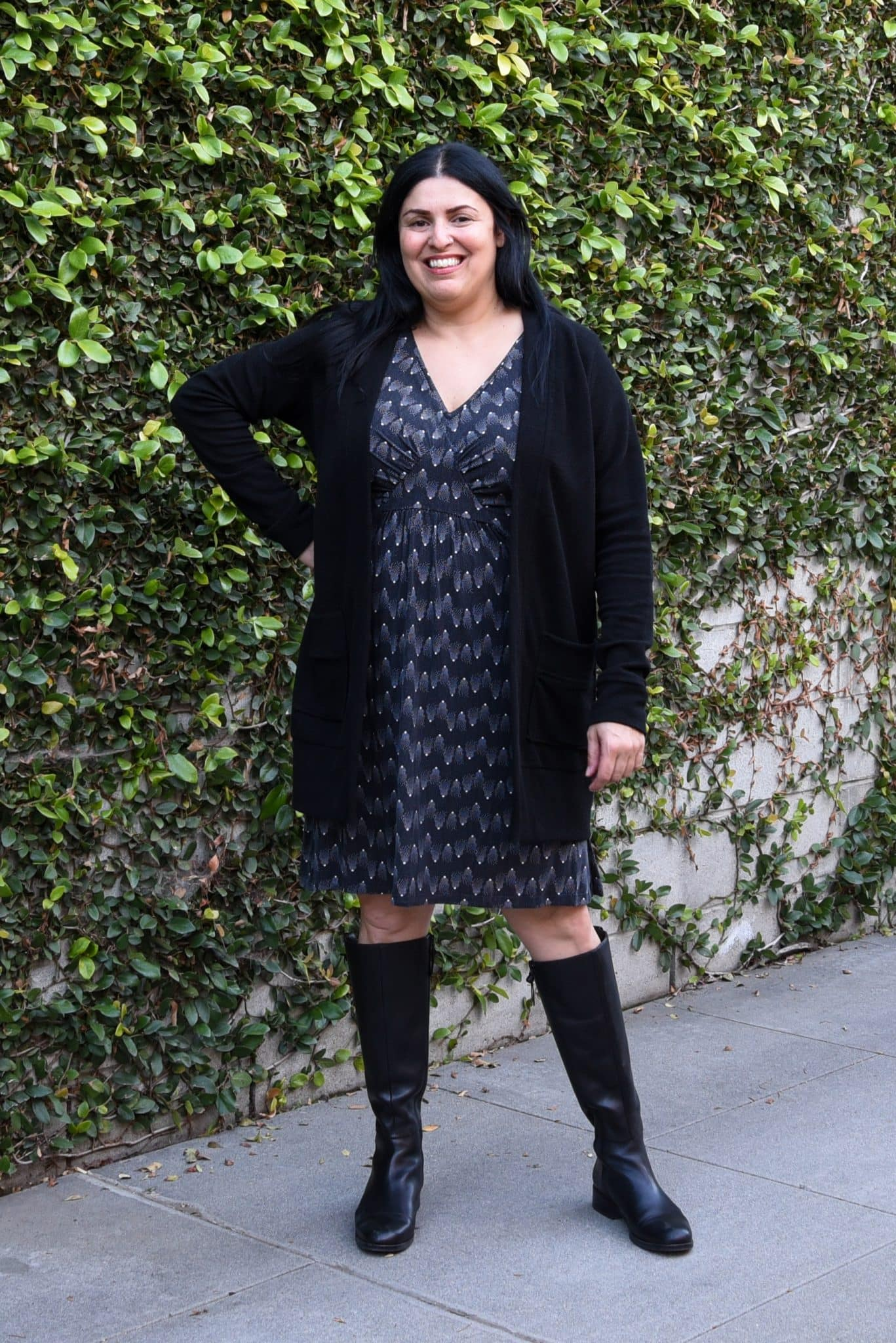Image of woman wearing a long, black cardigan and a black dress