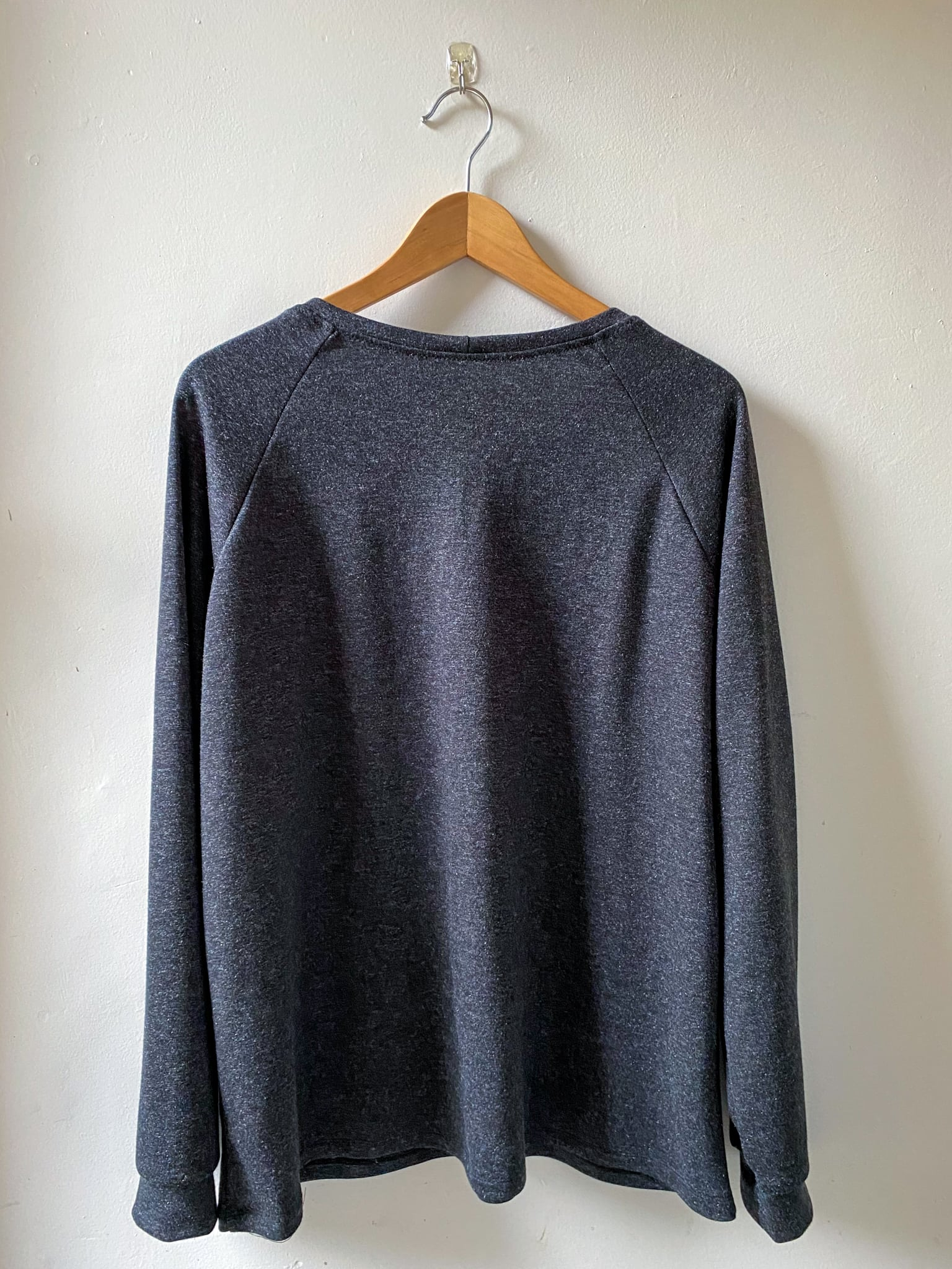 Image of the back of a dark gray Grainline Linden hanging from a hanger against a white background