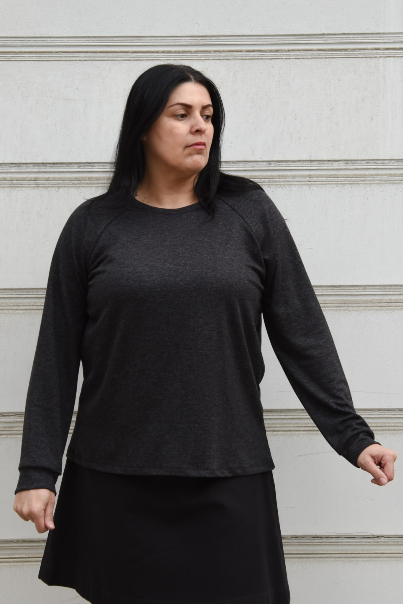 Image of a woman wearing a dark gray Grainline Linden sweatshirt and a black skirt standing in front of a white background