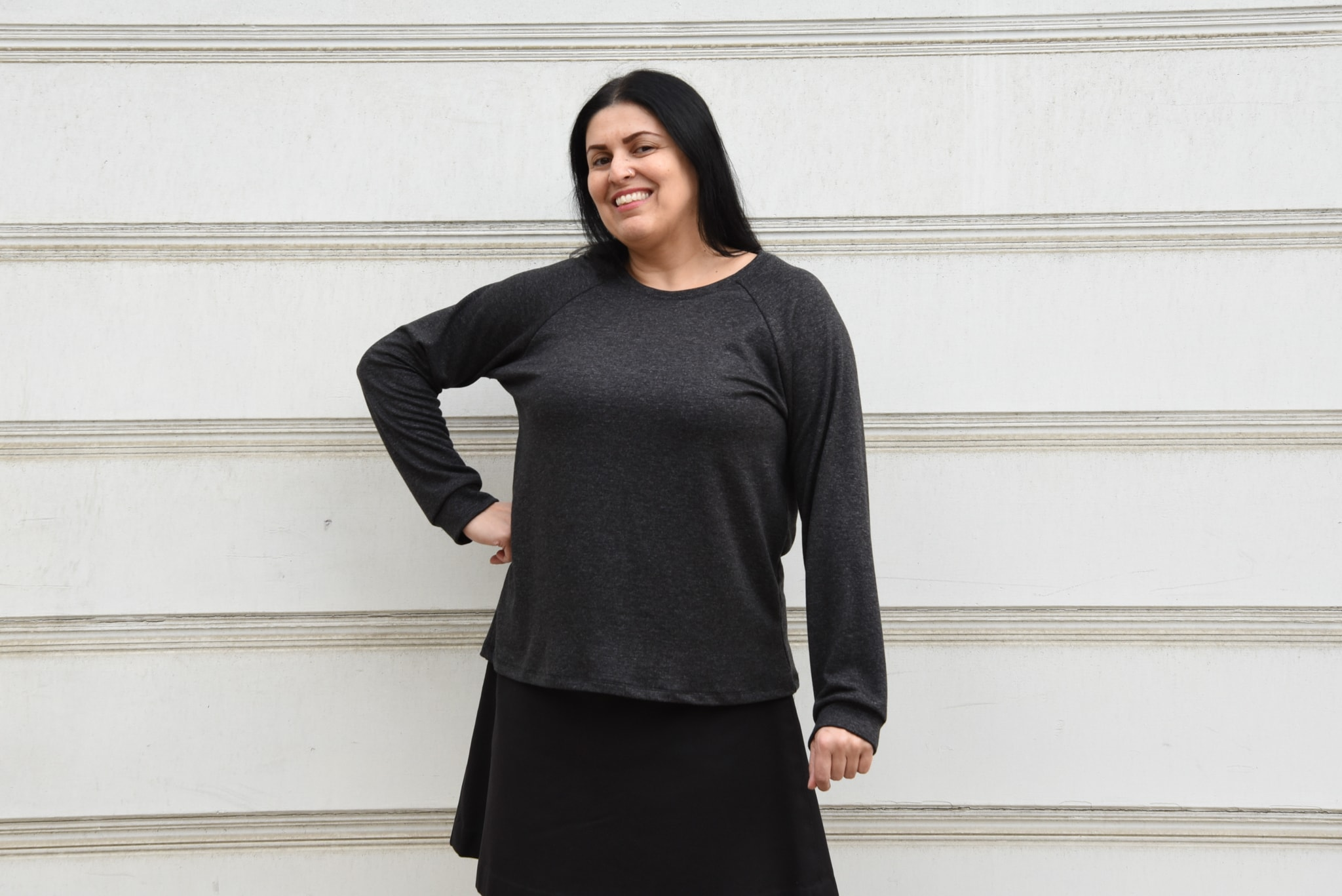 Image of a woman smiling at the camera wearing a dark gray Grainline Linden sweatshirt and a black skirt standing in front of a white background