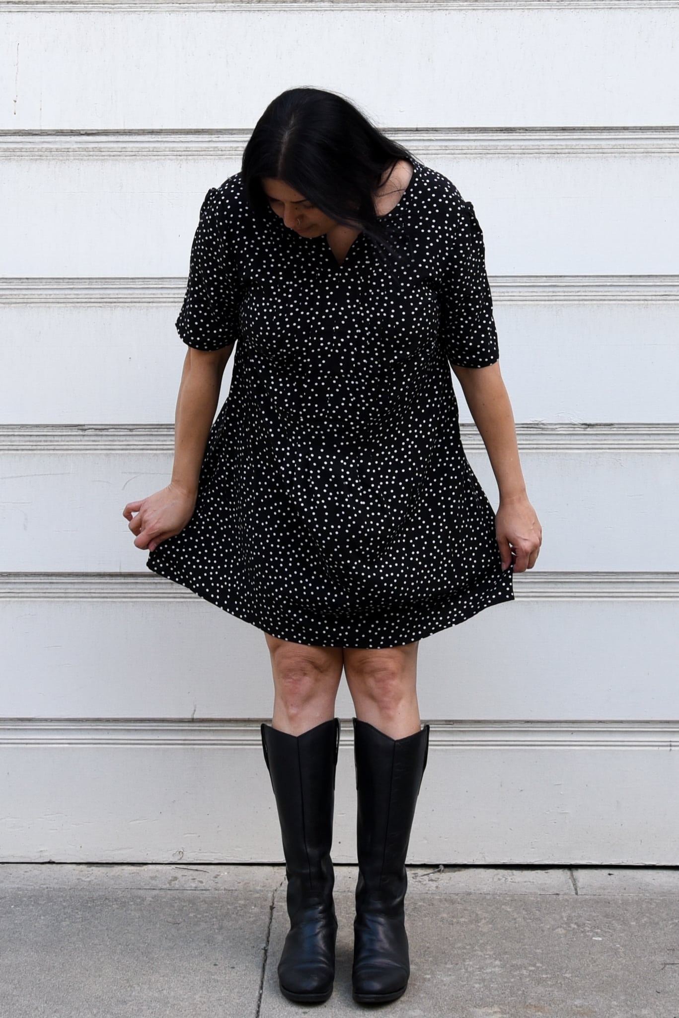 Image of woman leaning forward standing in front of a white background wearing a polka dotted black and white mini dress