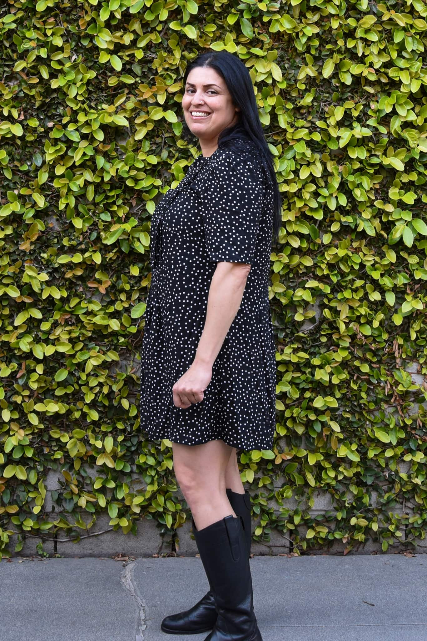 Image of woman standing sideways wearing a black and white polka dot Simplicity 8551 dress