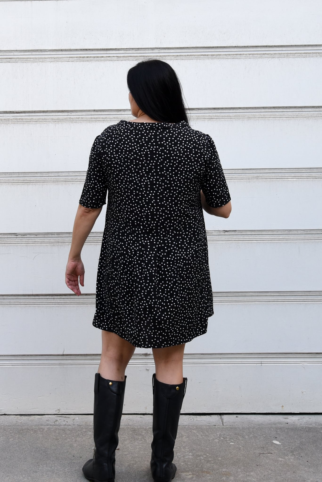 Image of woman with her back to the camera standing in front of a white background wearing a polka dotted black and white mini dress.