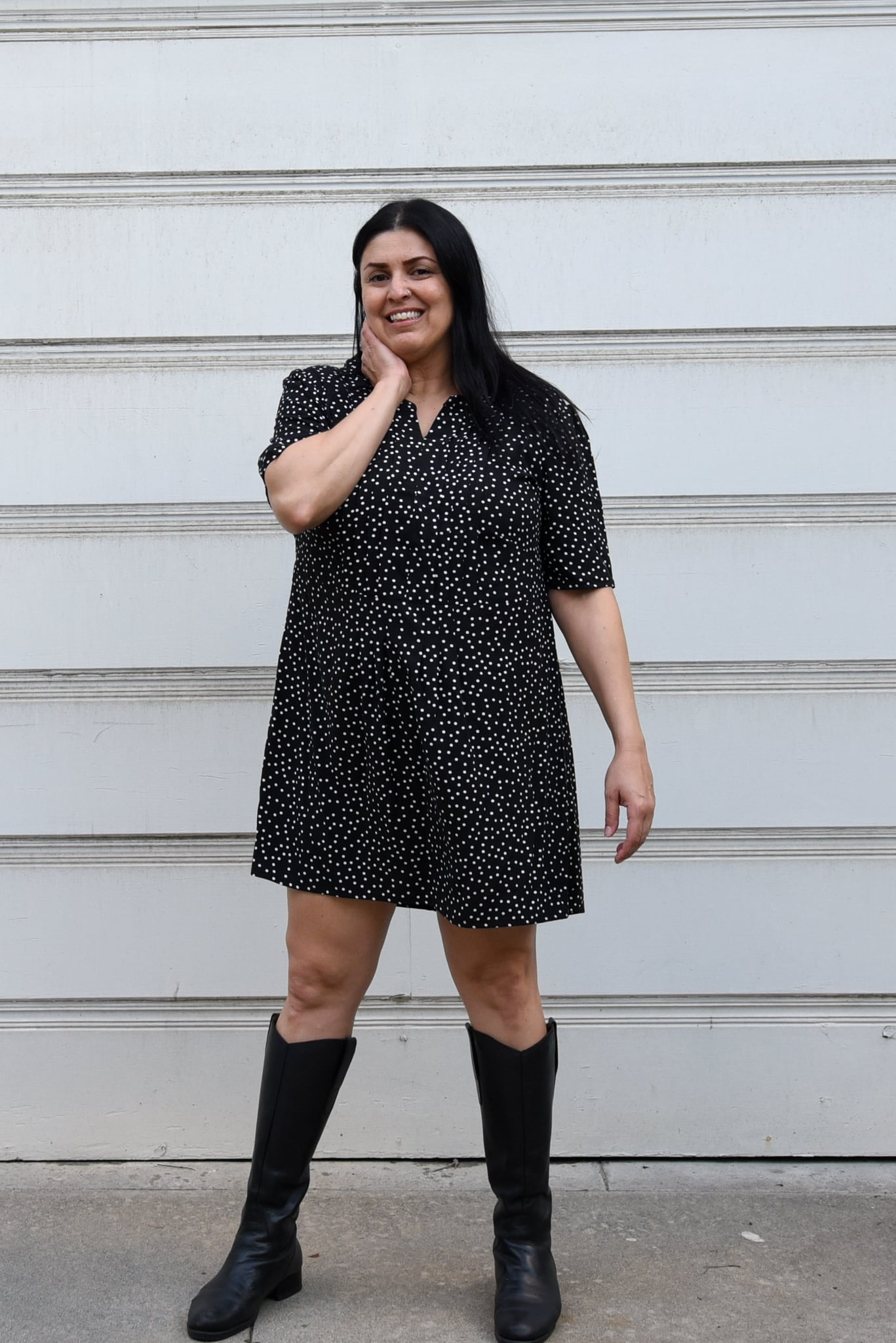 Image of woman standing in front of a white background wearing a polka dotted black and white mini dress.
