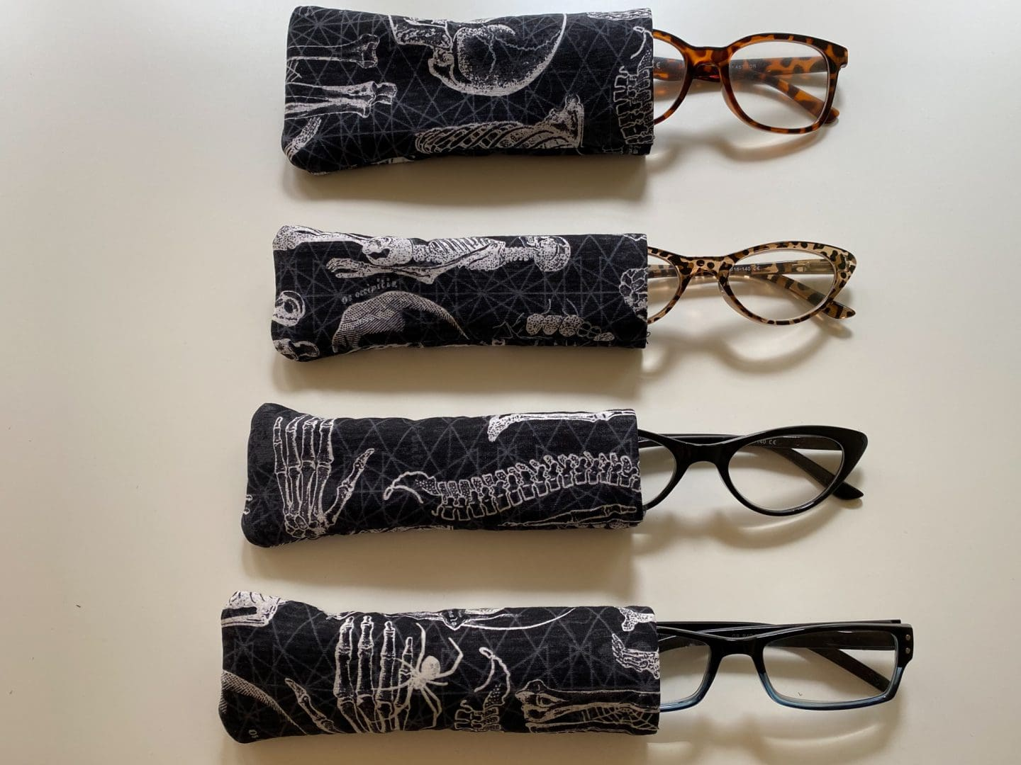 Image of four pairs of reading glasses peaking out of fabric cases with skeleton print