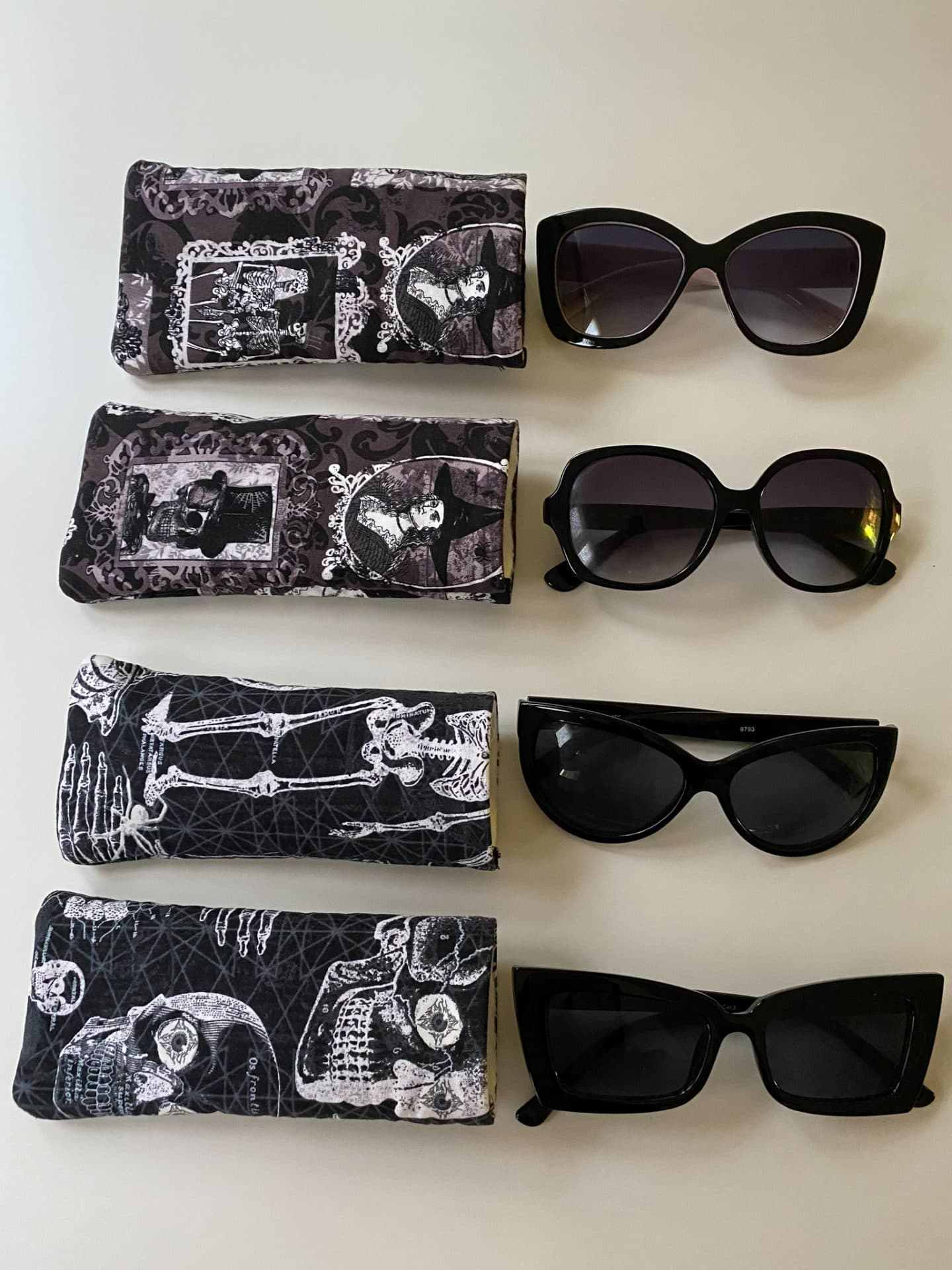 Image of sunglasses lined up on a white surface, each paired up with a case