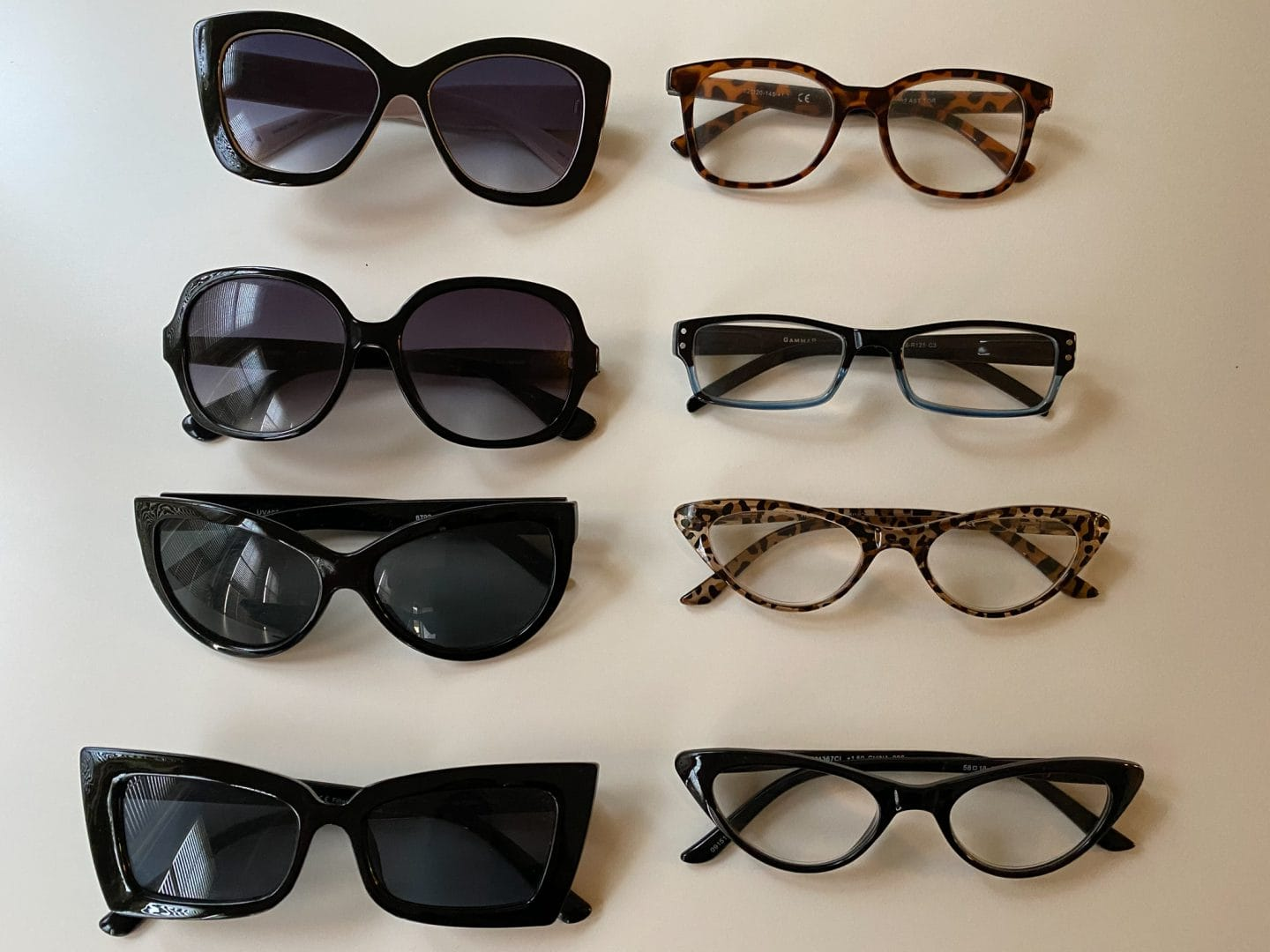 Image of two rows of glasses, one of sunglasses, the other reading glasses, against a white background.