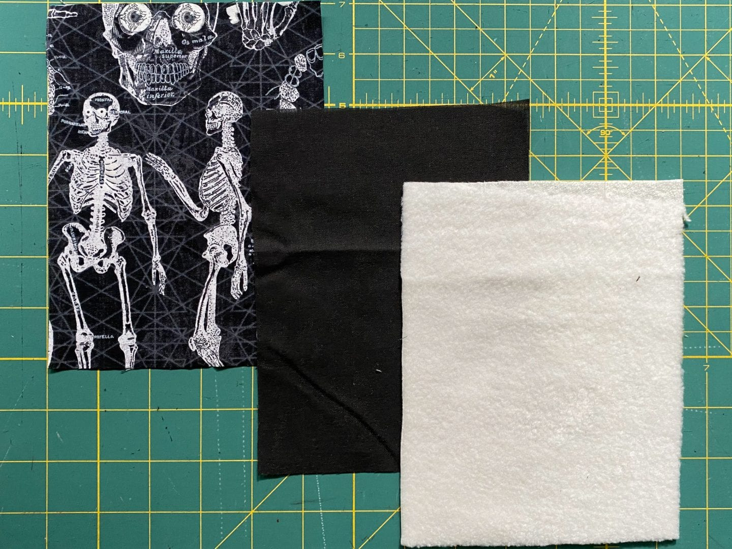 Image of three cuts of fabric, one with skeleton print, one of black interfacing, and one of cream-colored fleece.