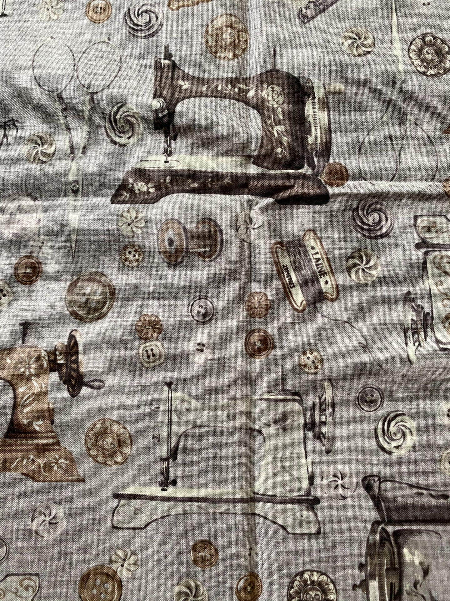 Image of fabric with vintage sewing machines, thread spools, and buttons as print against a grayish background.