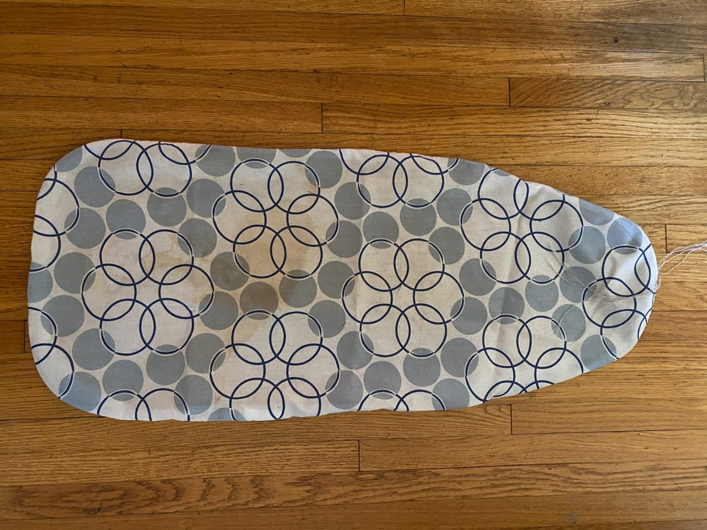 Image of an old, stained ironing board cover