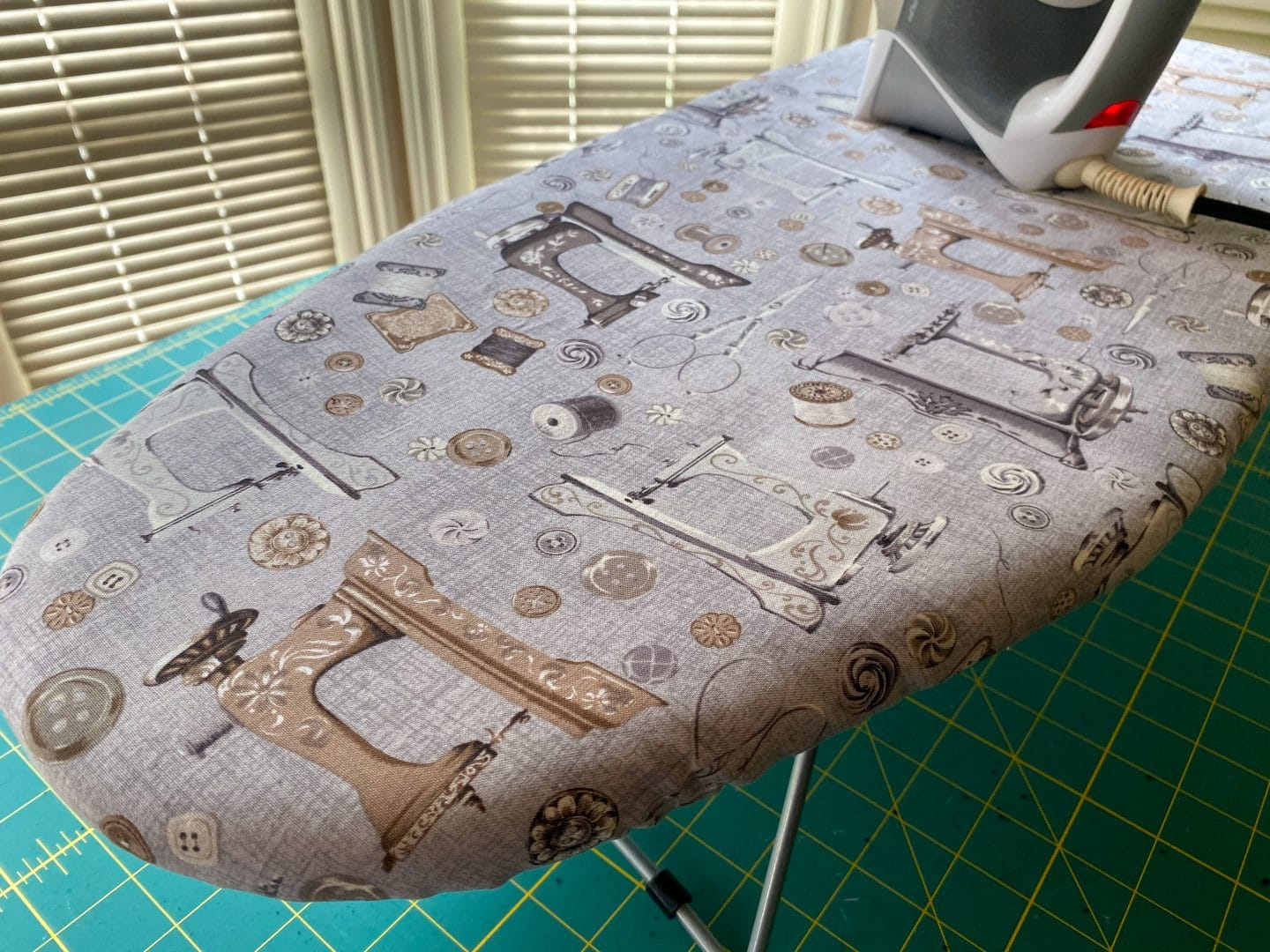 Image of an ironing board with a cover made of fabric with vintage sewing machines