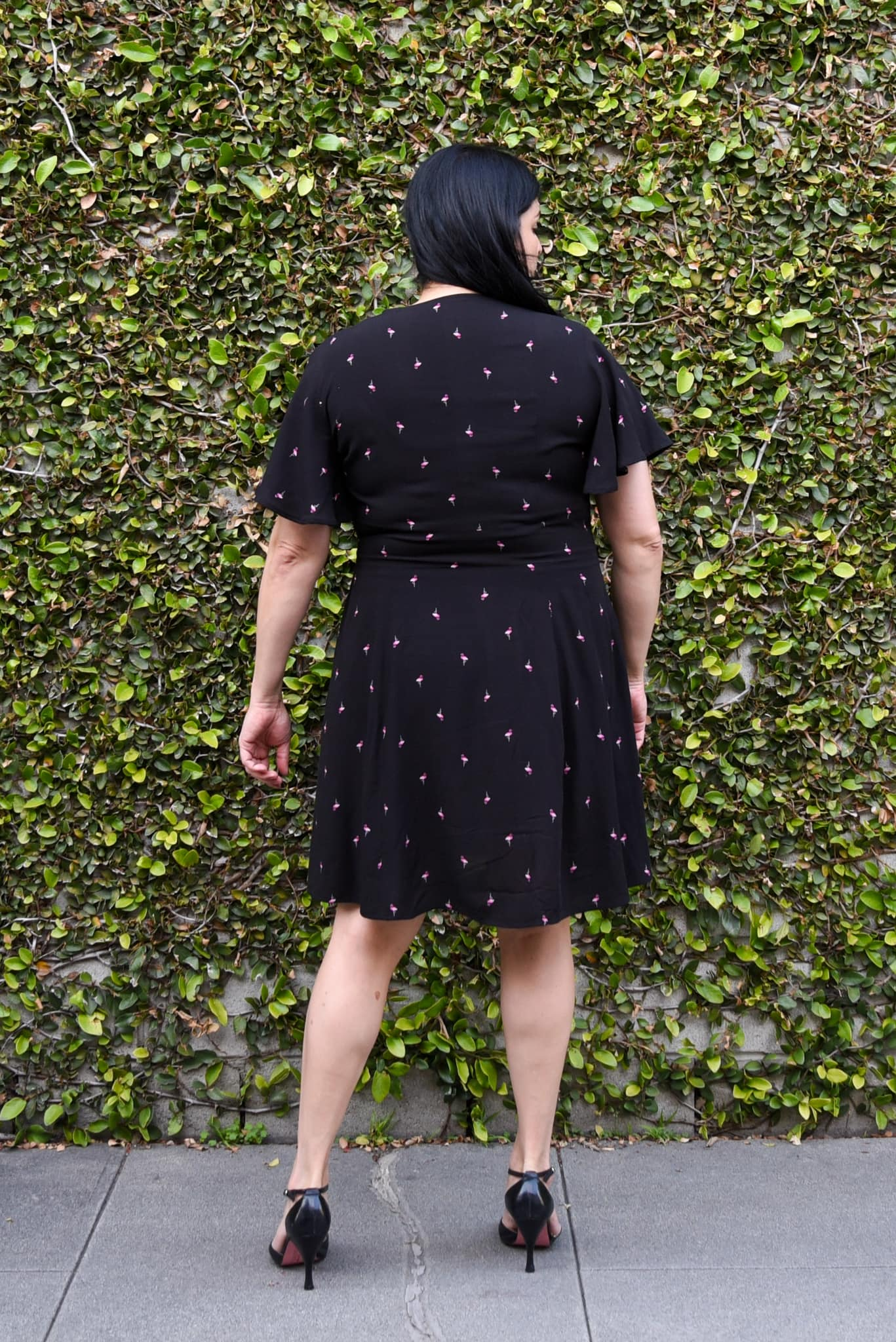 Image of a woman with long black hair wearing a Magnolia dress in black with tiny pink flamingos scattered like polka dots standing with her back to the camera in front of a wall covered by ivy.