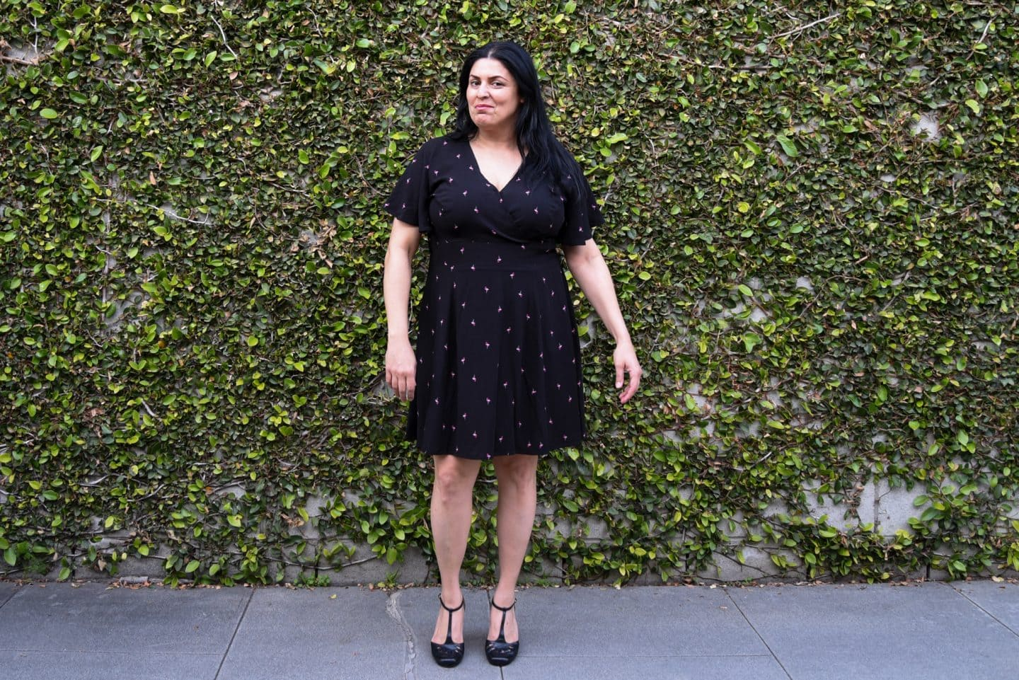 Image of a woman with long black hair wearing a Magnolia dress in black with tiny pink flamingos scattered like polka dots standing in front of a wall covered by ivy.