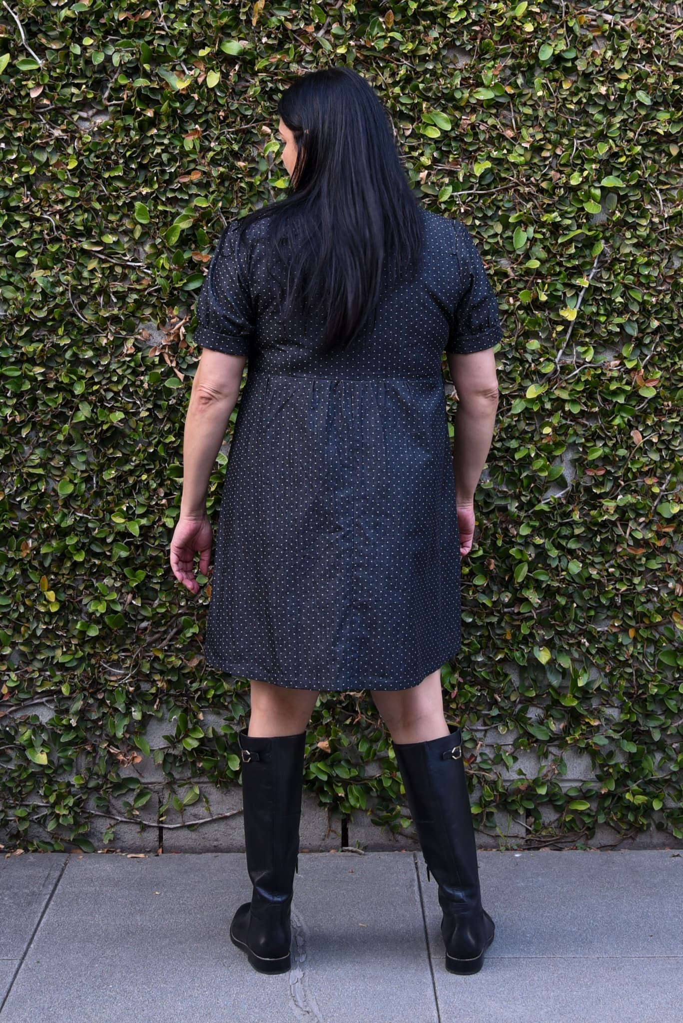 Image of woman standing with her back to the camera in front of an ivy-covered wall wearing a fauxwrap dress in a black cotton chambray with white polka dots.