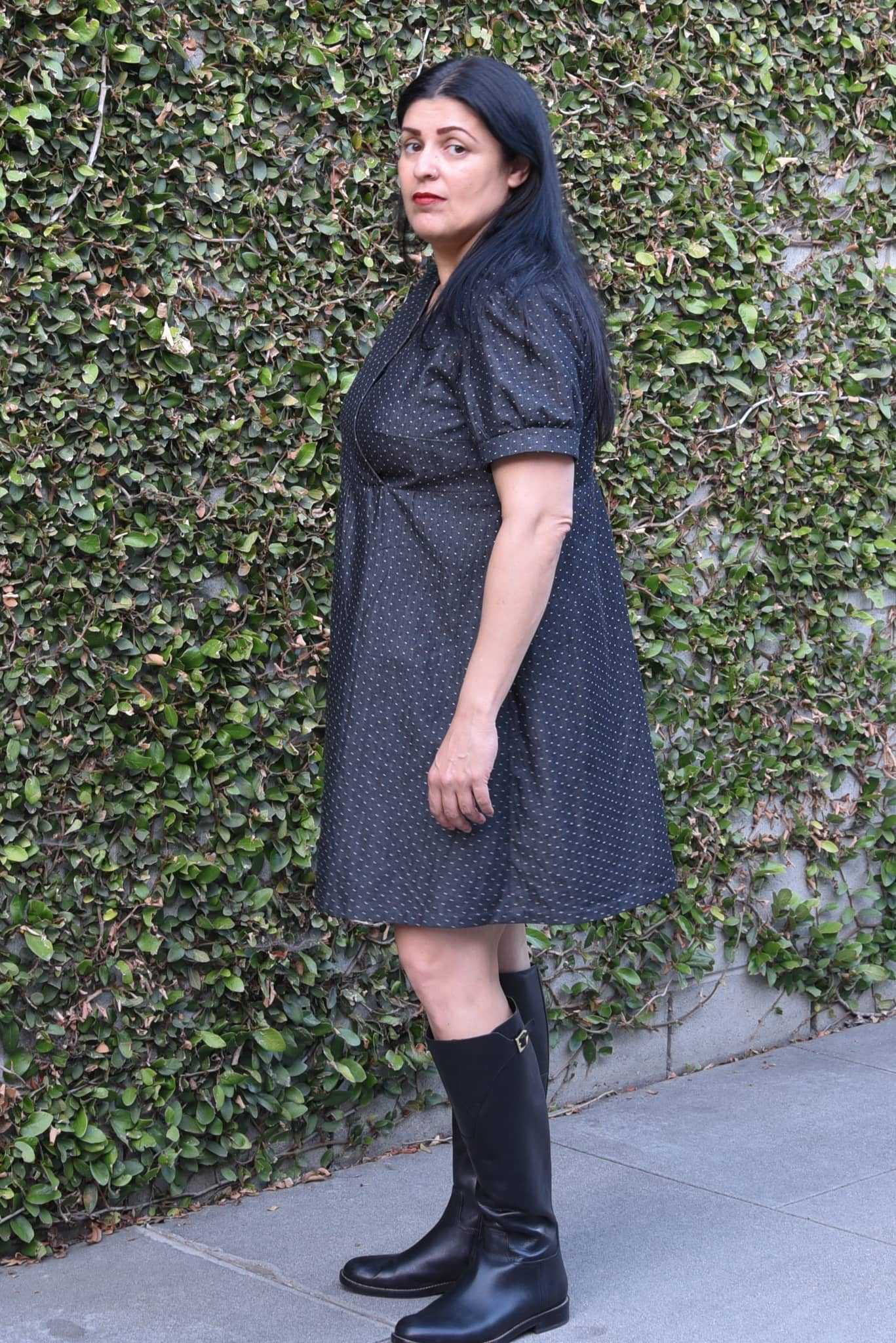 Image of woman standing in front of an ivy-covered wall wearing a fauxwrap dress in a black cotton chambray with white polka dots.