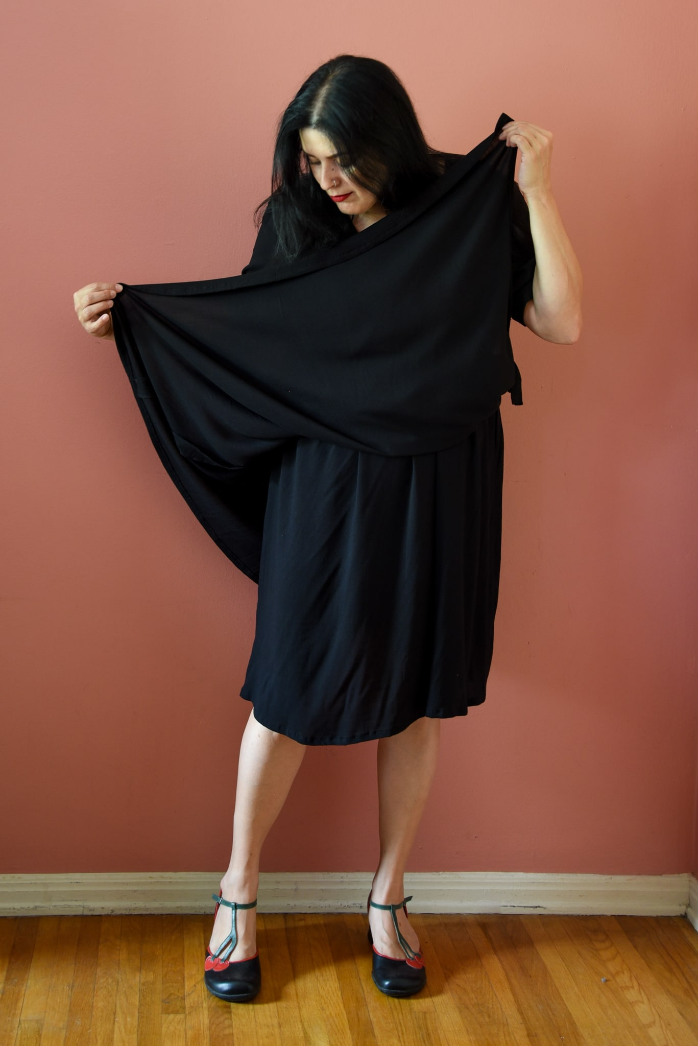 Image of a woman wearing a black wrap dress while demonstrating how the underskirt keeps the dress from revealing skin.