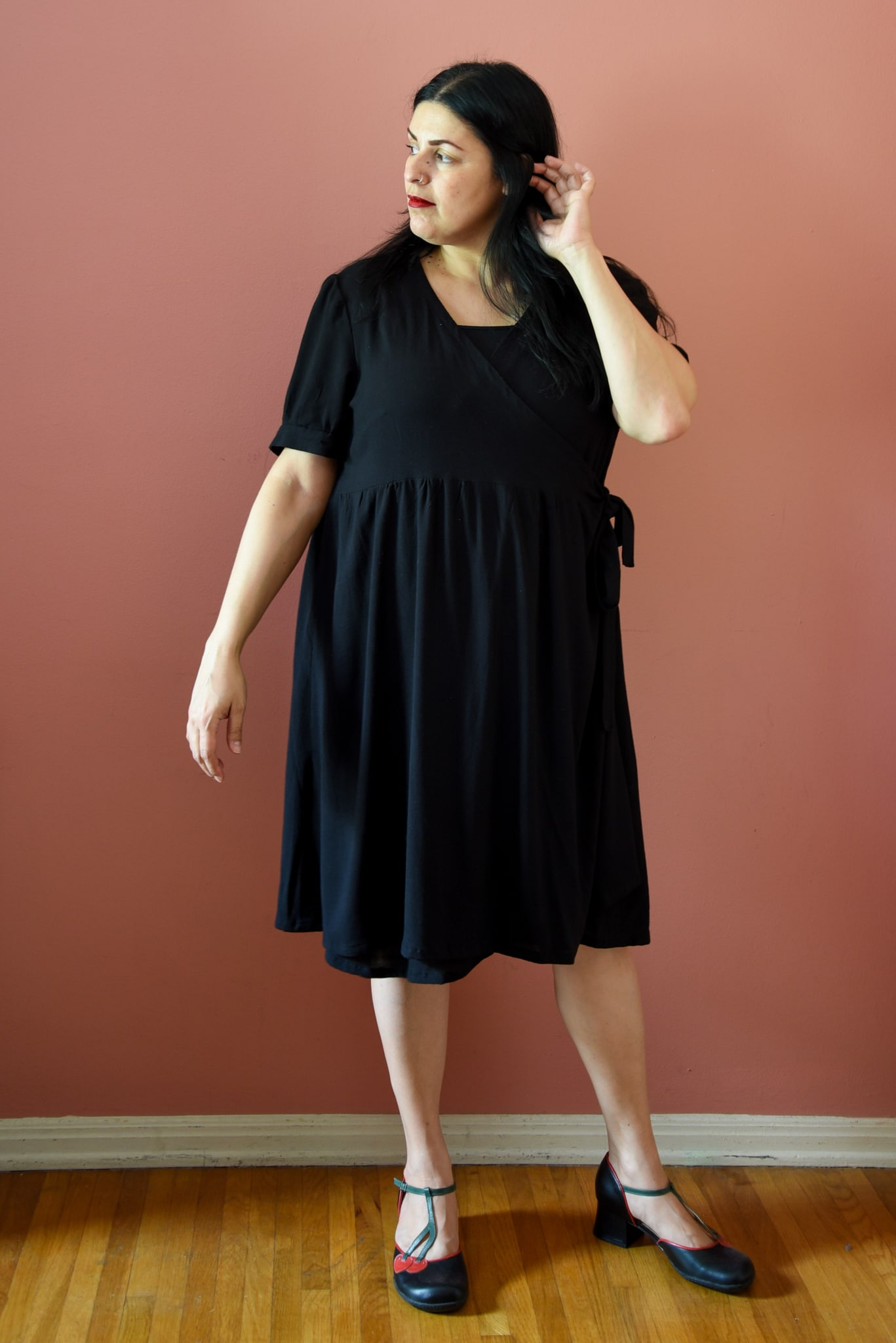 Image of a woman wearing a black wrap dress standing in front of a pink wall.