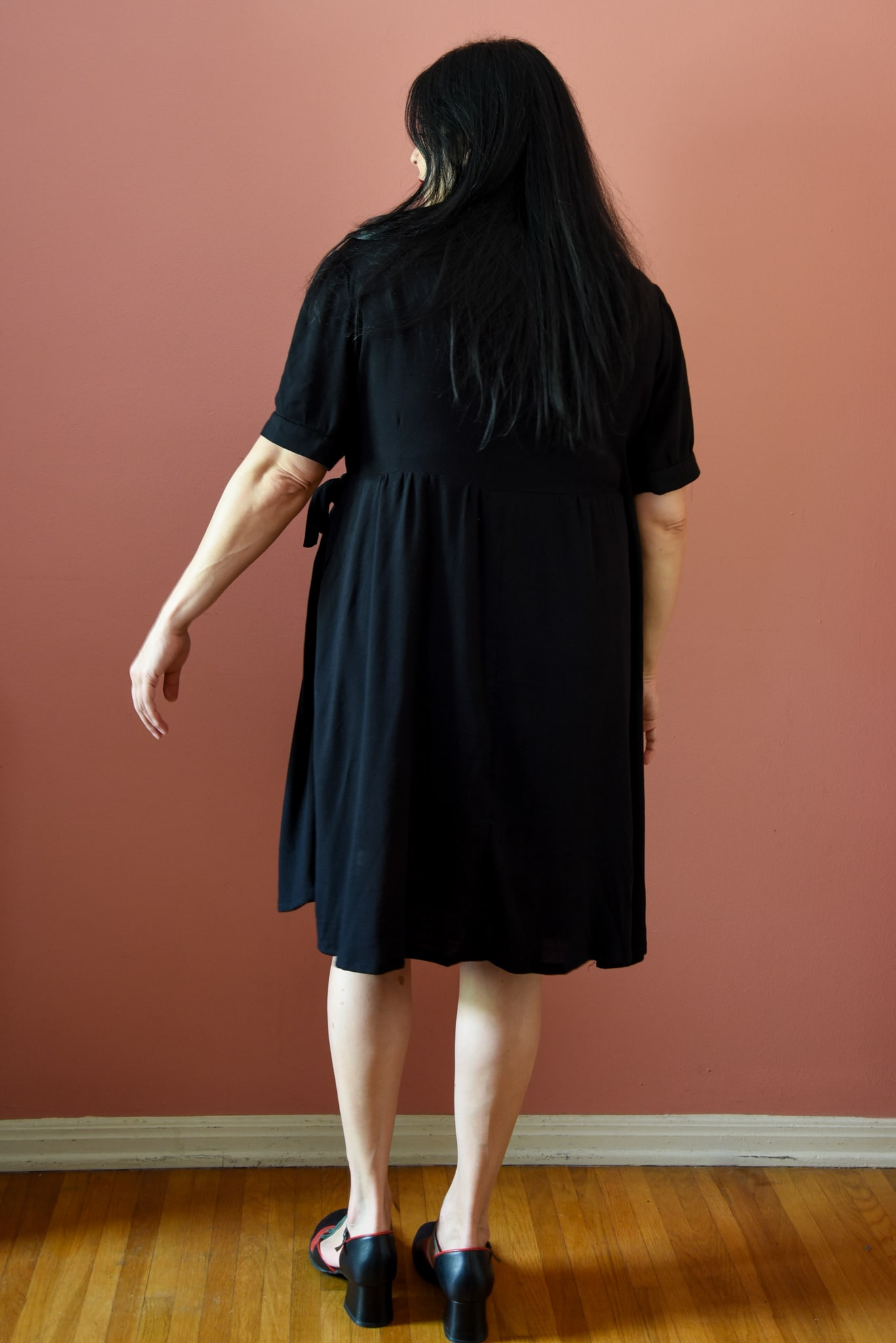 Image of the back of a woman wearing a black wrap dress standing in front of a pink wall.