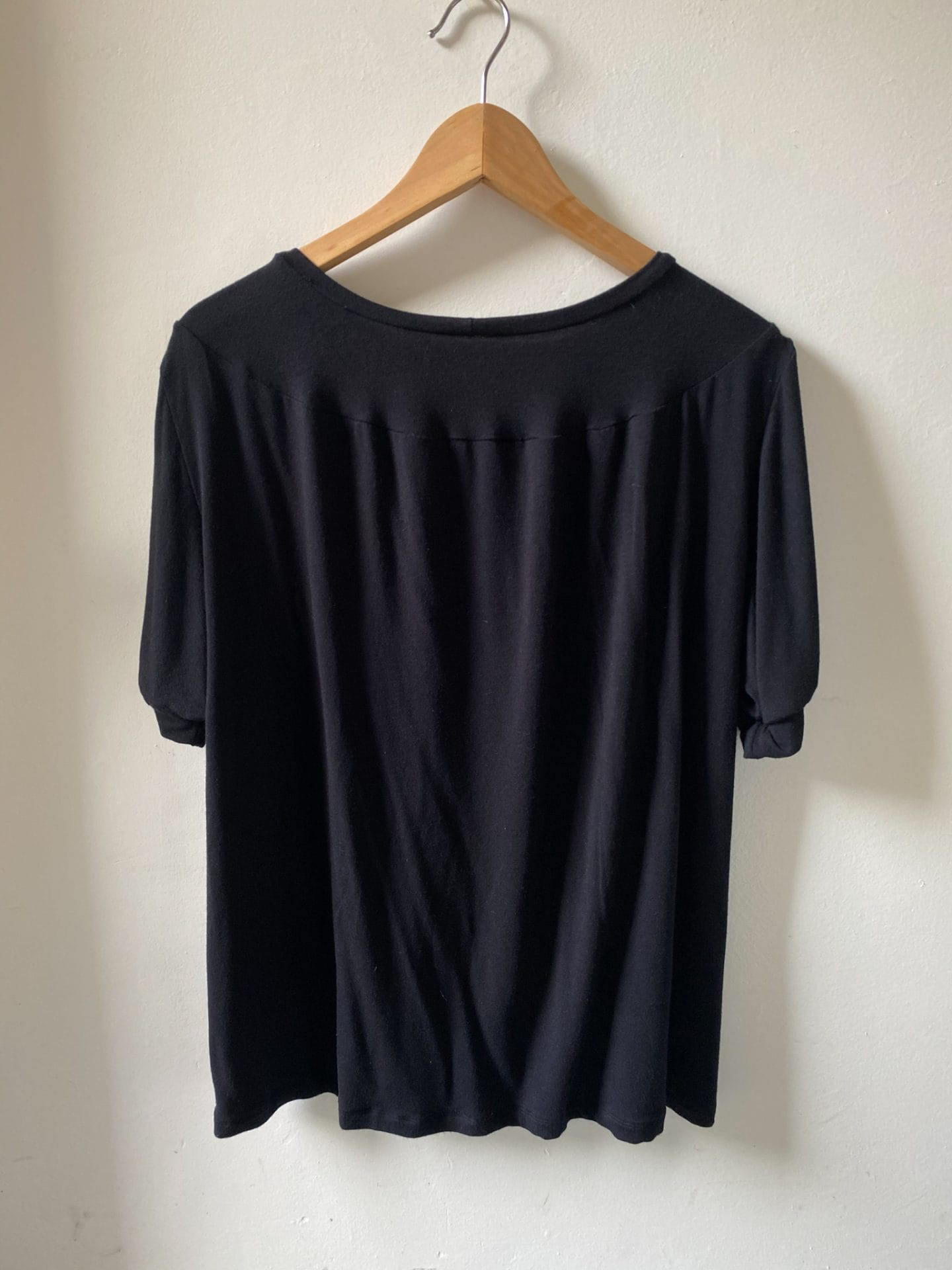 Image of T-shirt hanging from a hanger showing detail of back of the garment