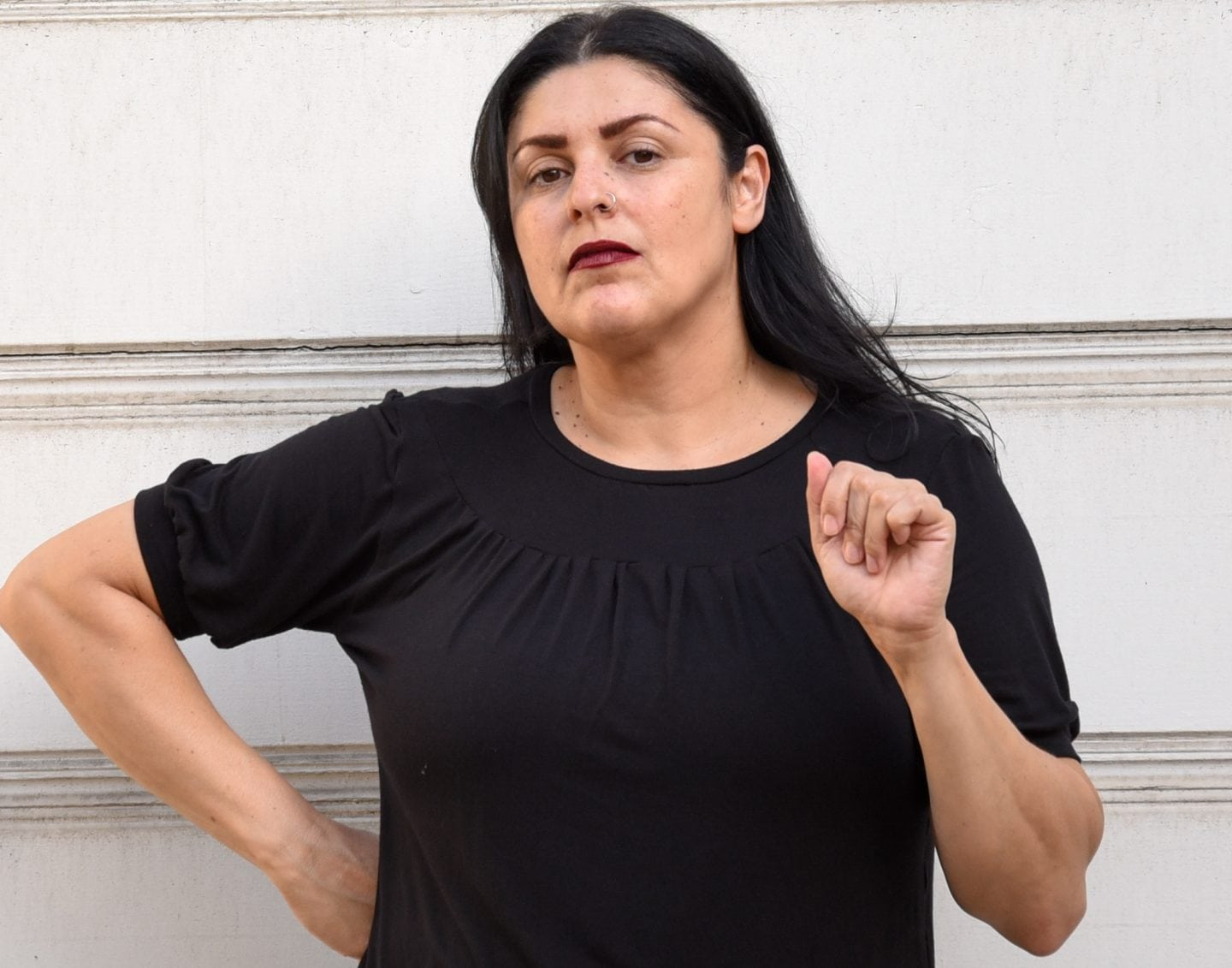 Image of a woman wearing a black T-shirt with gathering below the neck