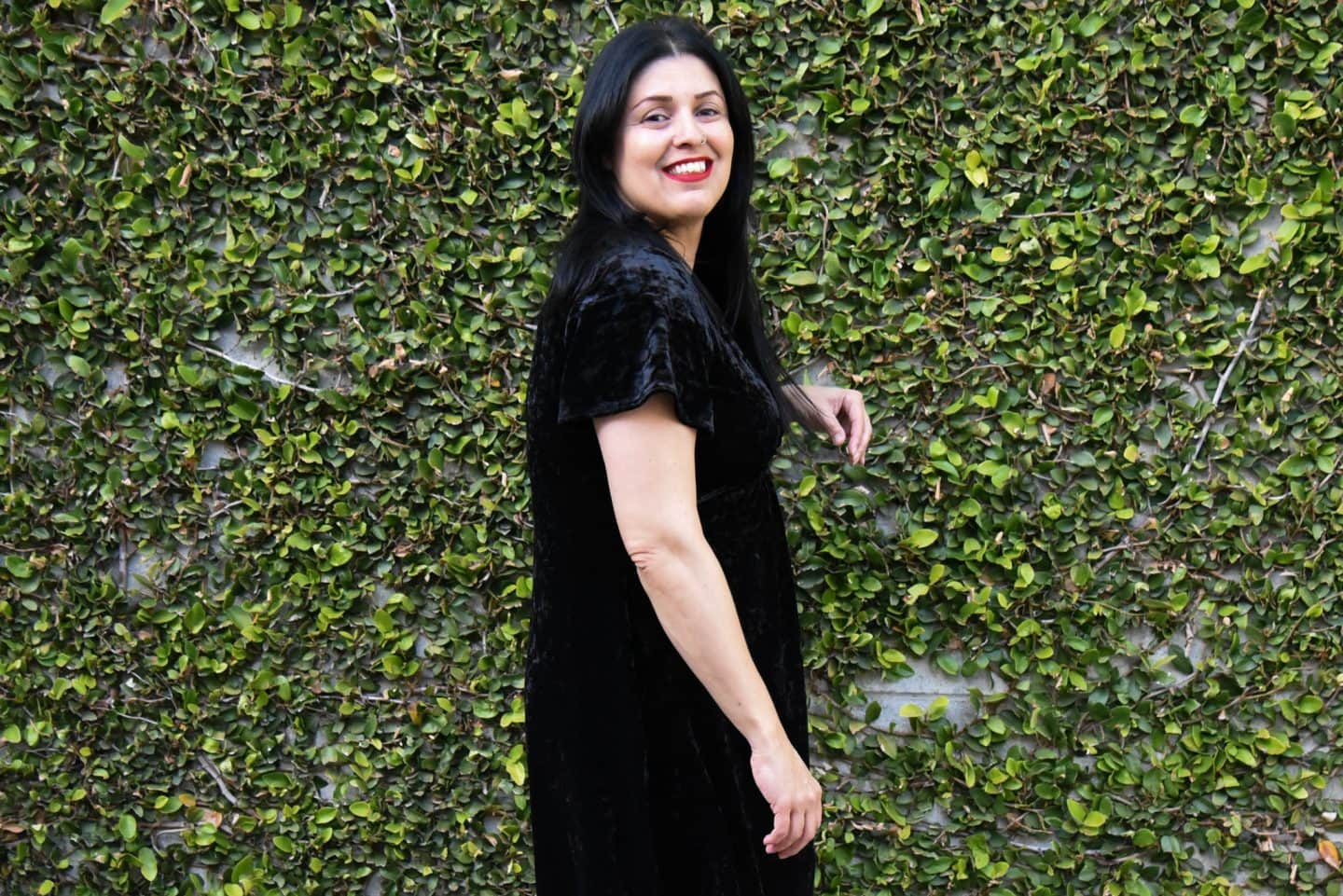Image of woman with long black hair standing sideways to the camera wearing a black velvet dress with flutter sleeves in front of a wall covered in vines