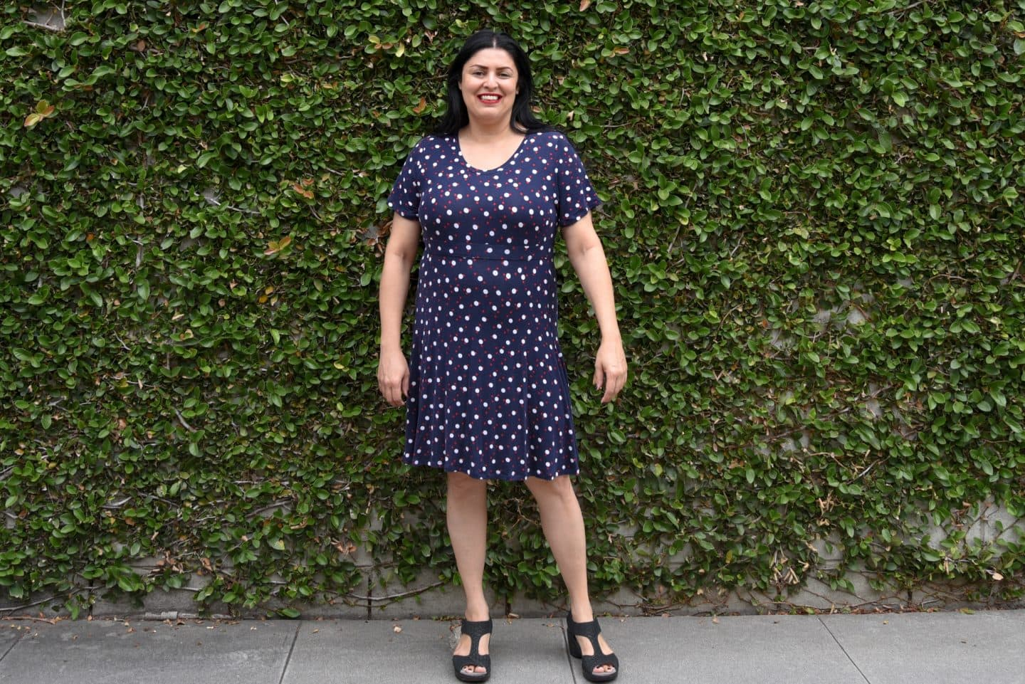 Image of woman with long black hair looking to the right standing in front of a wall covered in vines wearing an empires dress in a dark blue knit with larger white polka dots and smaller red polka dots