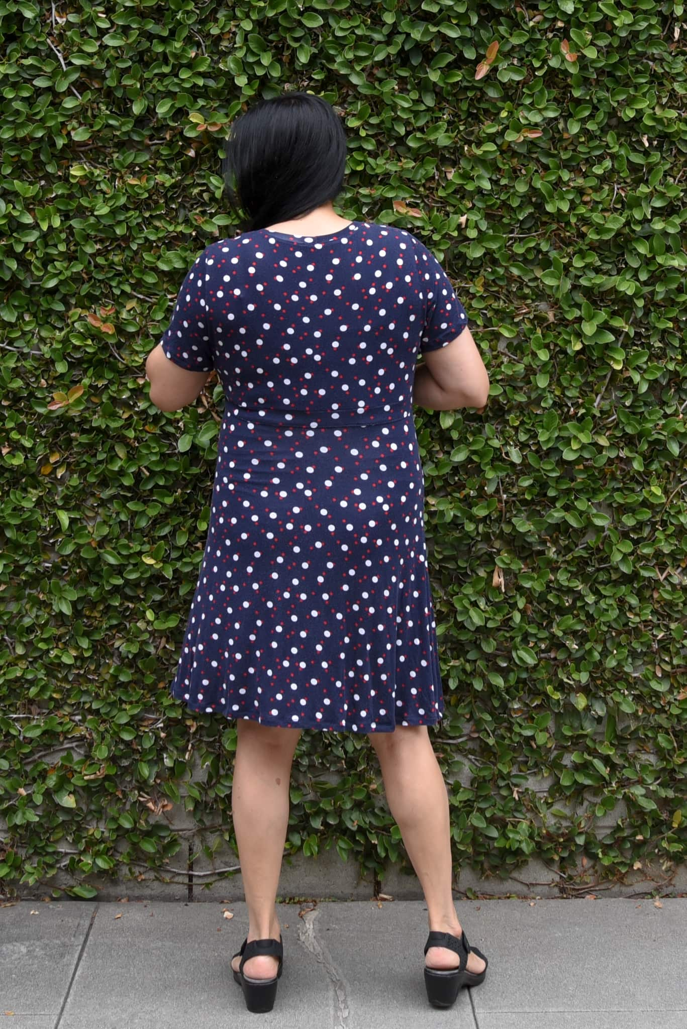 Image of woman with long black hair with her back to the camera standing in front of a wall covered in vines wearing an empire dress in a dark blue knit with larger white polka dots and smaller red polka dots