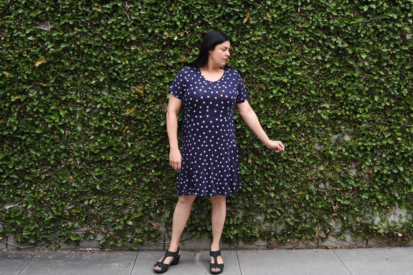 Image of woman with long black hair looking to the left standing in front of a wall covered in vines wearing an empires dress in a dark blue knit with larger white polka dots and smaller red polka dots