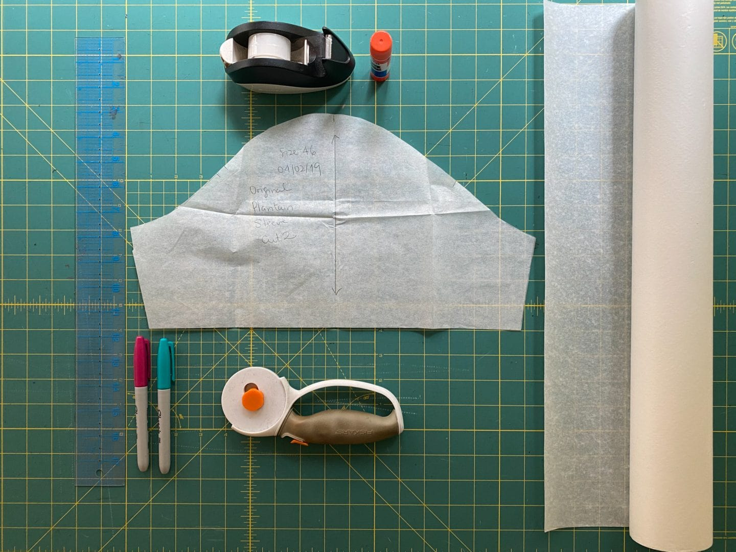 Image of materials to hack sleeve pattern: pattern piece, ruler, markers, tape/glue, cutter/scissors, and paper—lots of it!