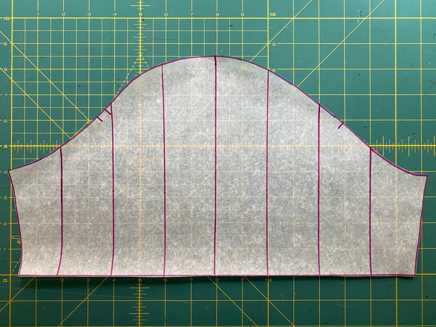 Image of the sleeve pattern with pink lines parallel to the grain line used as guide to cut into the pattern on a green background.