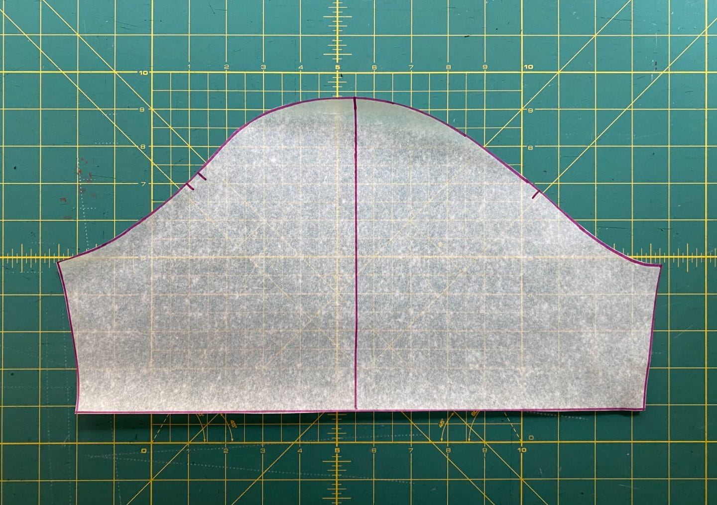 Image of the sleeve pattern with a pink line from the center notch all the way down on a green background.