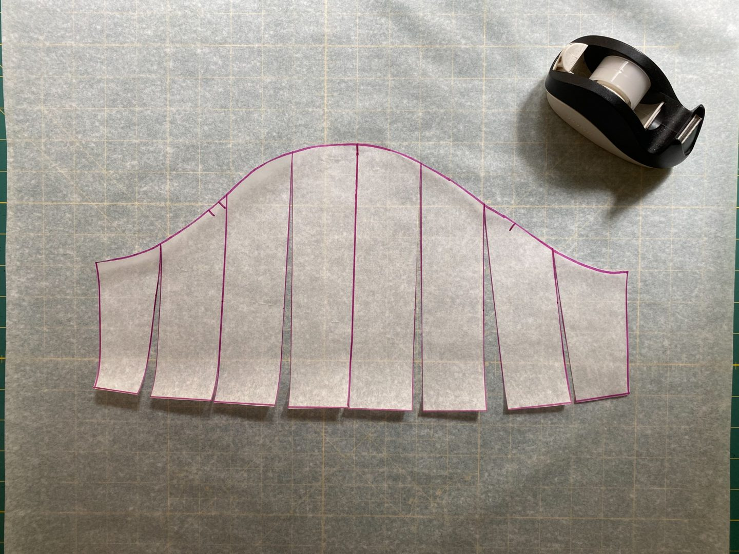 Image of the slashed sleeve pattern taped to a larger piece of pattern under the pattern.