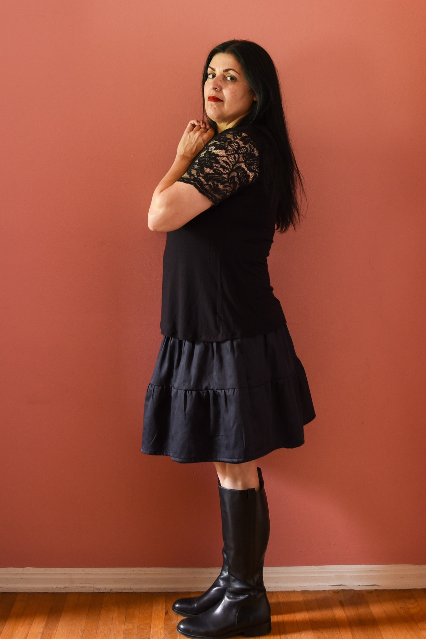 Image of a woman with long black hair standing sideways to the camera wearing a black top with lace sleeves, a black skirt with gathered panels, knee-high black books standing in front of a pink wall holding the skirt up to expose the lining of the skirt.