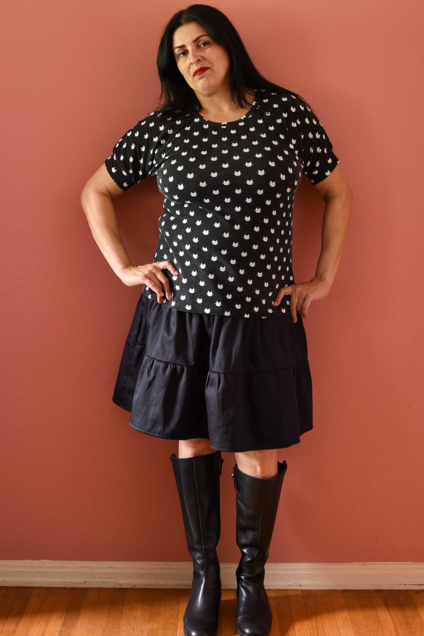 Image of woman with long black hair wearing a black and white polka dotted top with cat prints for dots and a black goth Lolita-sih skirt.